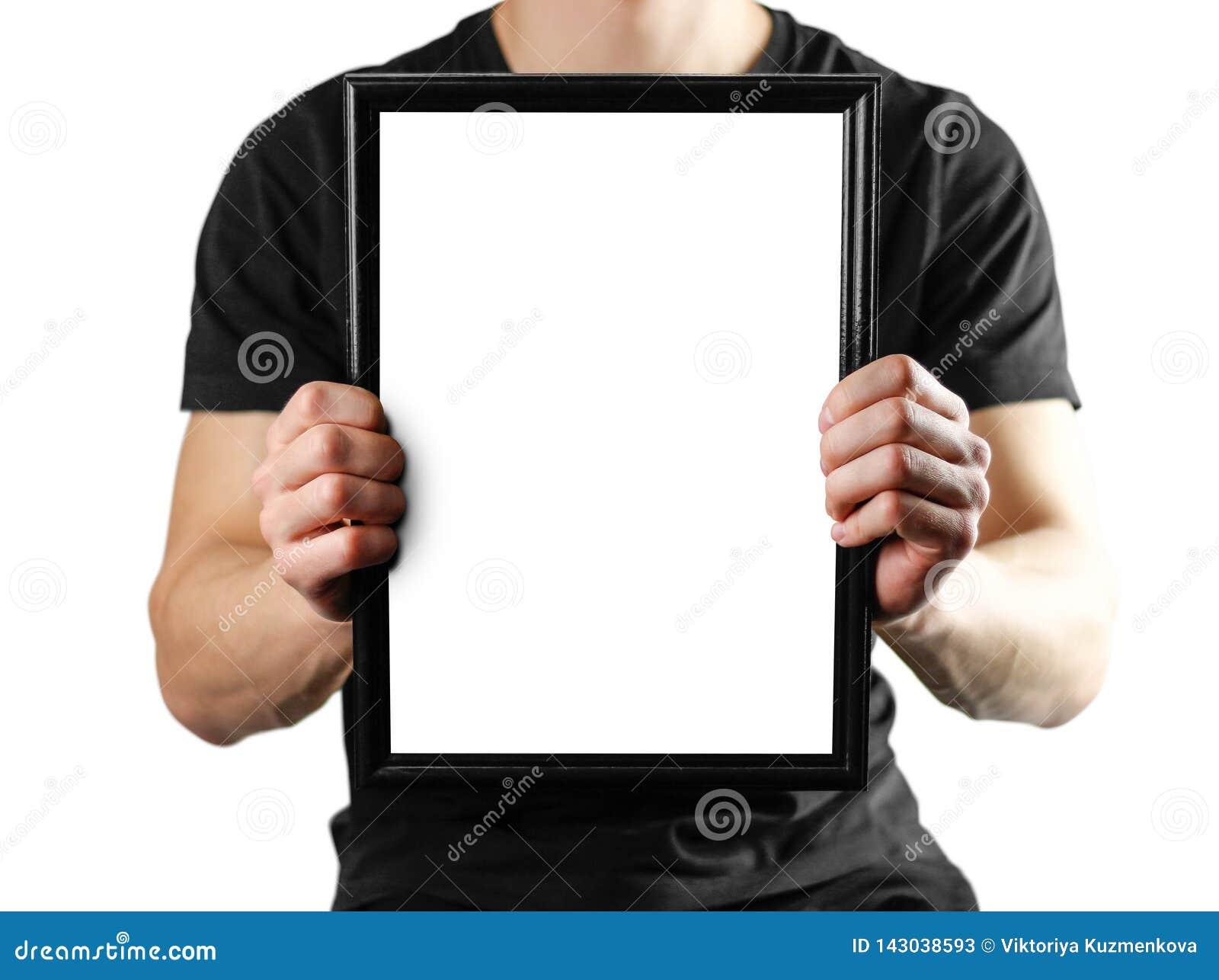Un hombre lleva a cabo un marco negro A4 Un marco vacío con un fondo blanco Cierre para arriba Aislado en el fondo blanco