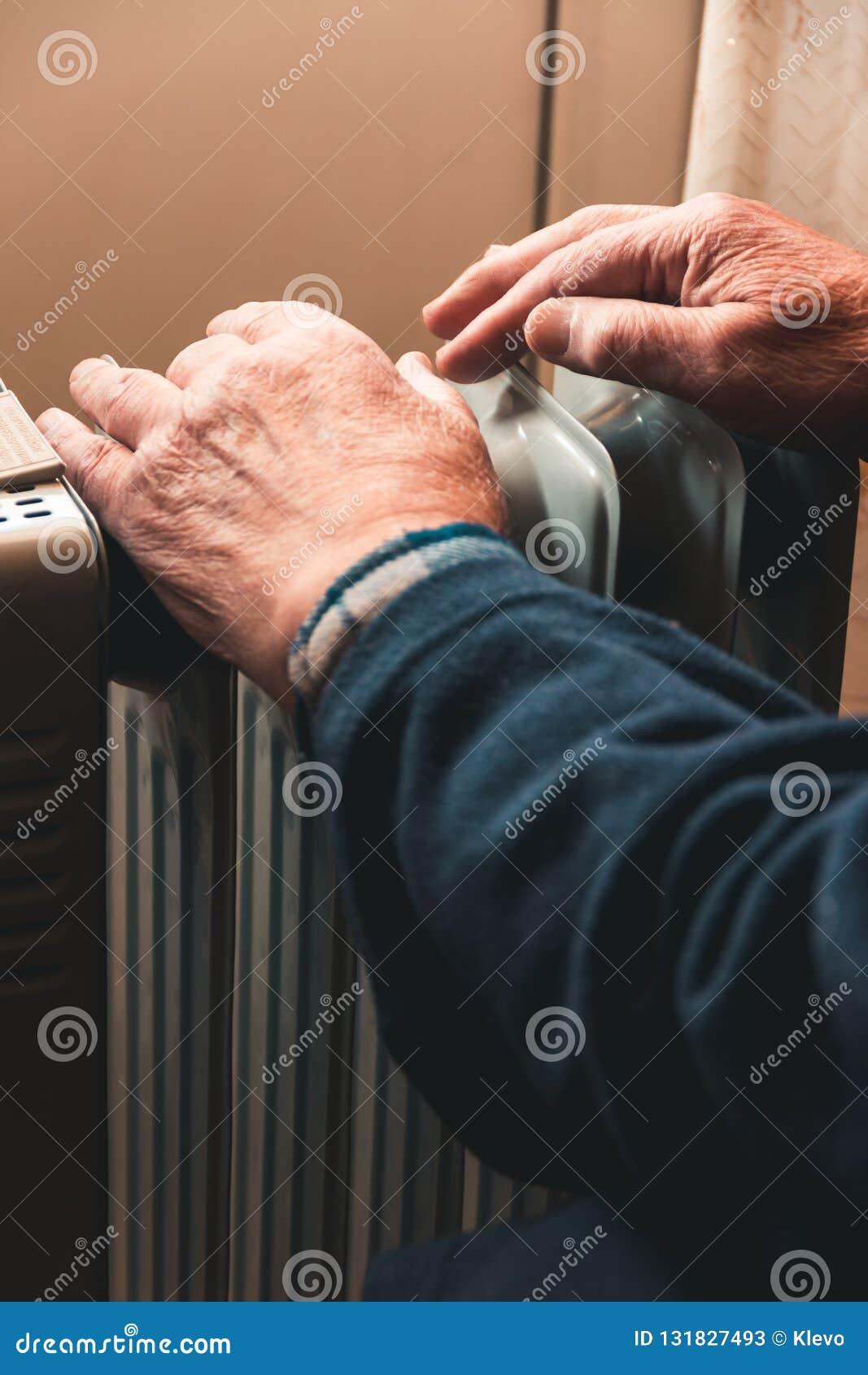 Un hombre mayor se calienta las manos sobre un calentador eléctrico En la temporada baja, se retrasa la calefacción central