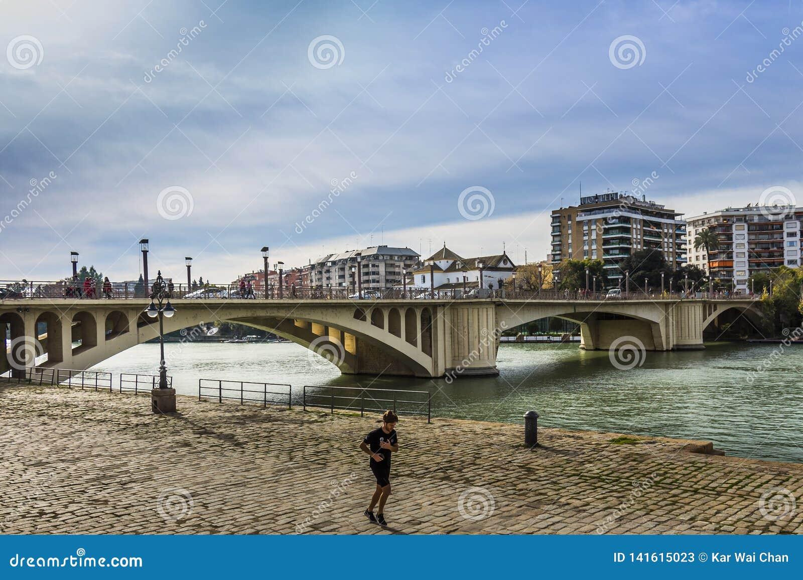 Un hombre que activa a lo largo del canal Alfonso XII después de San Telmo Bridge