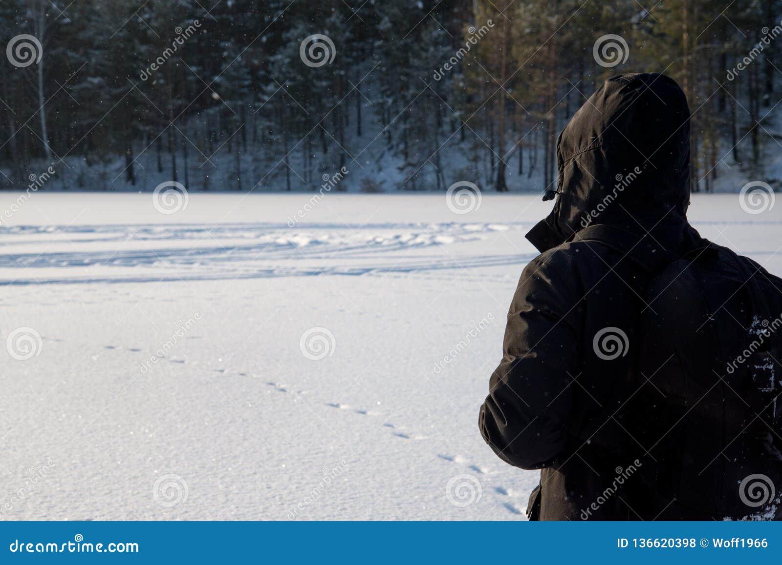 Un hombre que camina en la nieve Silueta de un hombre que camina en un llano nevoso