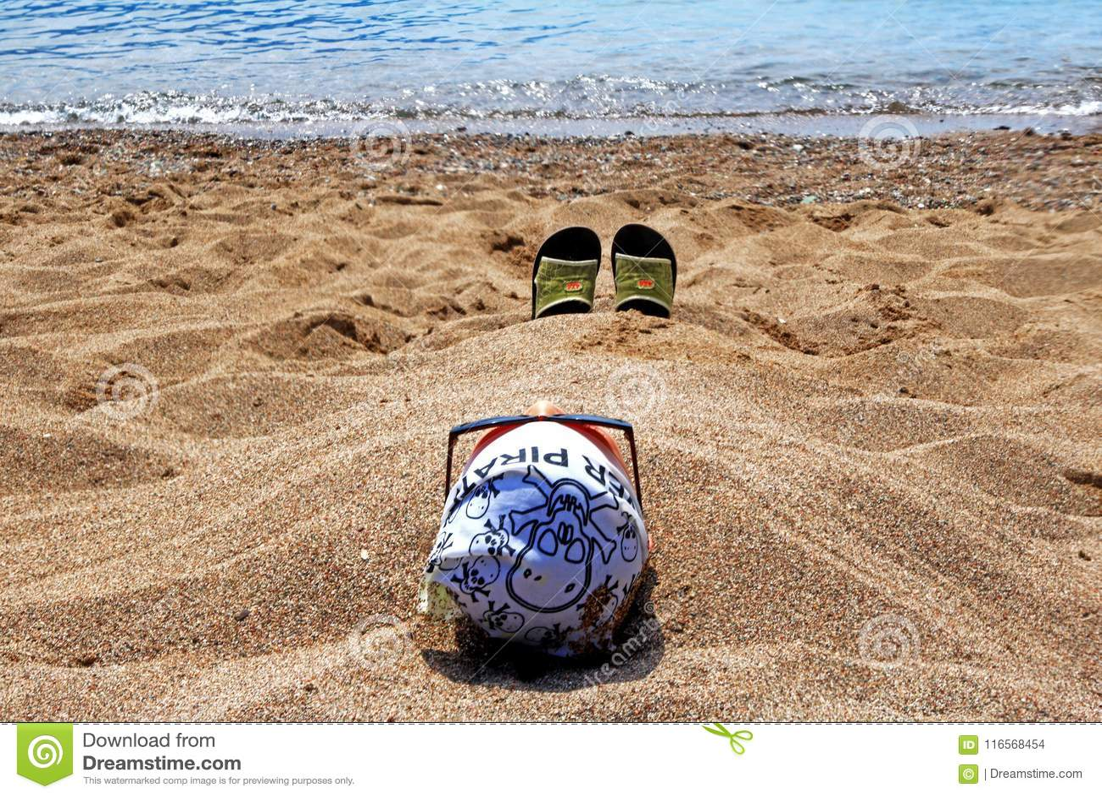 Un hombre que descansa sobre la costa, enterrada en arena caliente