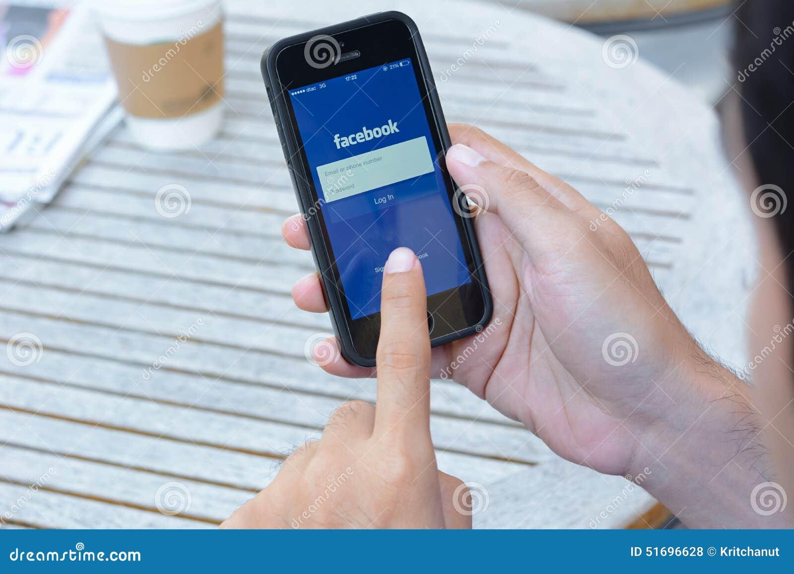 Un hombre que usa el uso de Fackbook en iphone