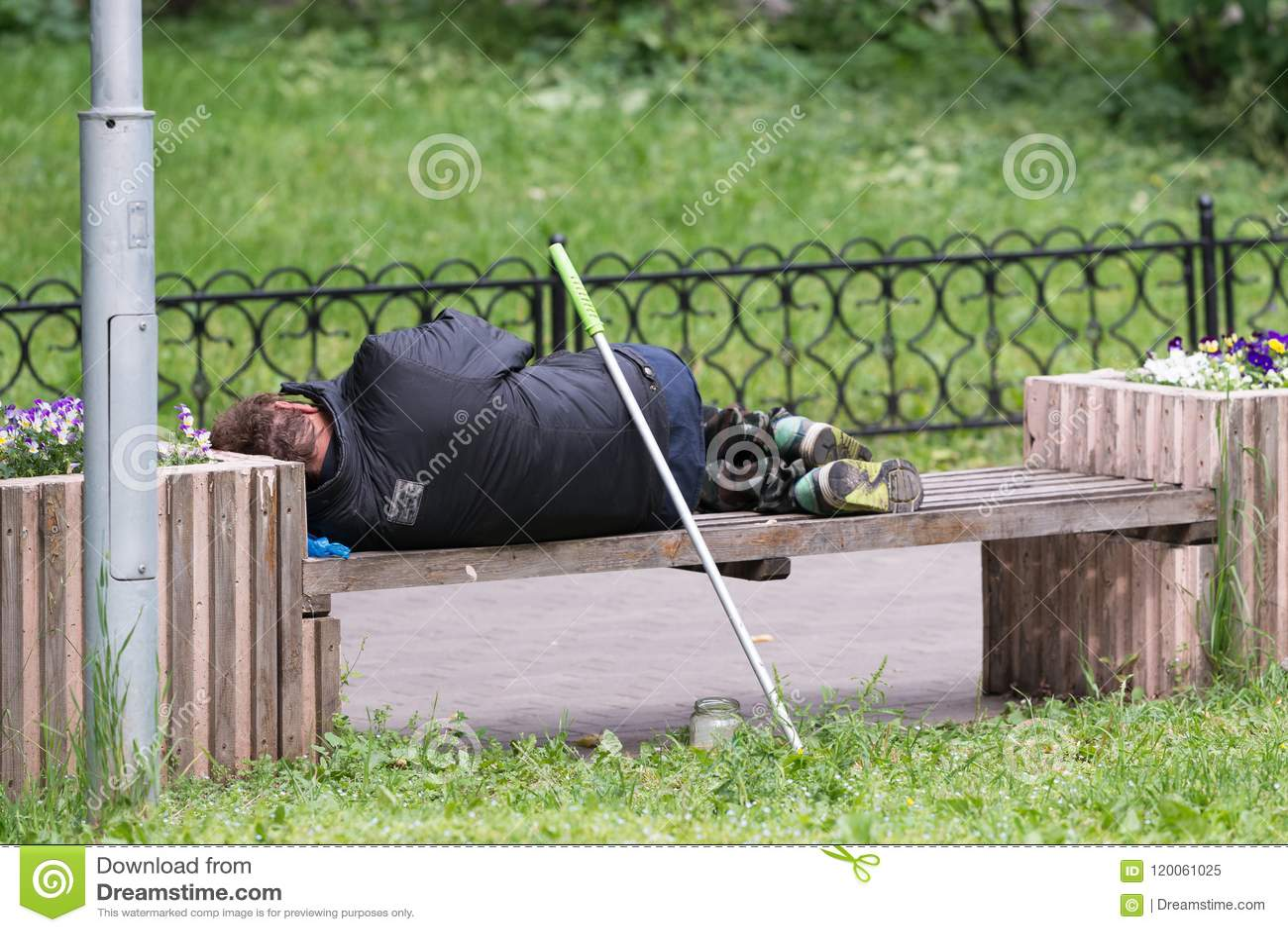 Un hombre sin hogar sucio que duerme en una chaqueta negra en un banco de la calle
