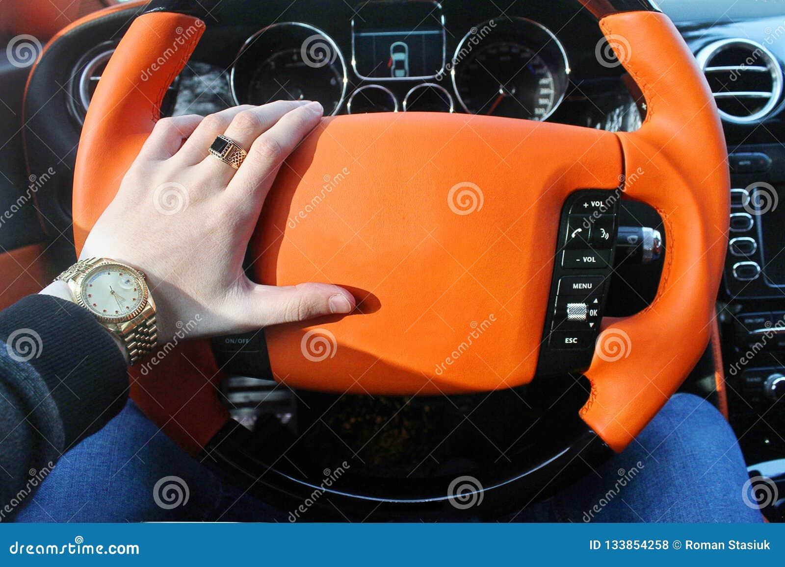 Un hombre sostiene el volante de un coche de lujo Reloj de oro y un anillo en su mano