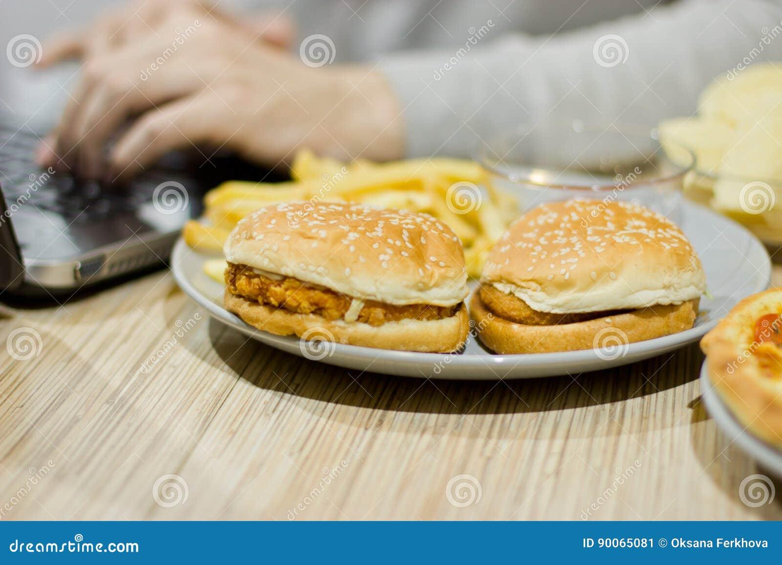 Un hombre trabaja en un ordenador y come los alimentos de preparación rápida comida malsana: BU