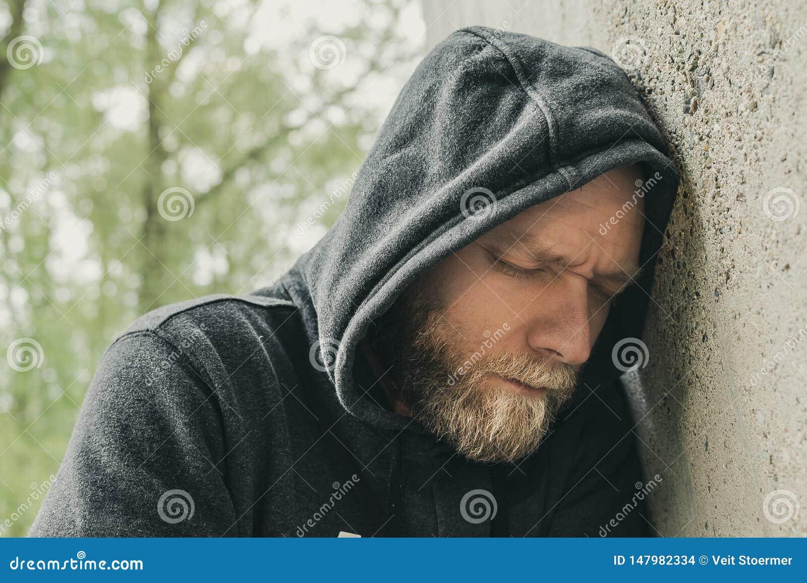Un hombre triste y solo en la pared