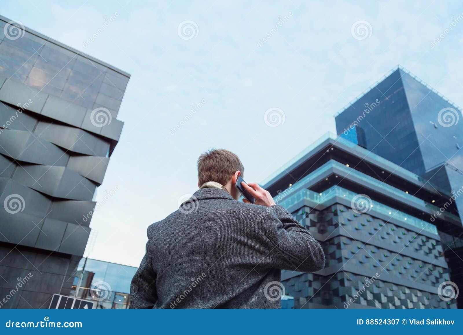 Un hombre vestido bonito que habla en un teléfono móvil delante de un rascacielos de la oficina Visión desde la parte posterior d