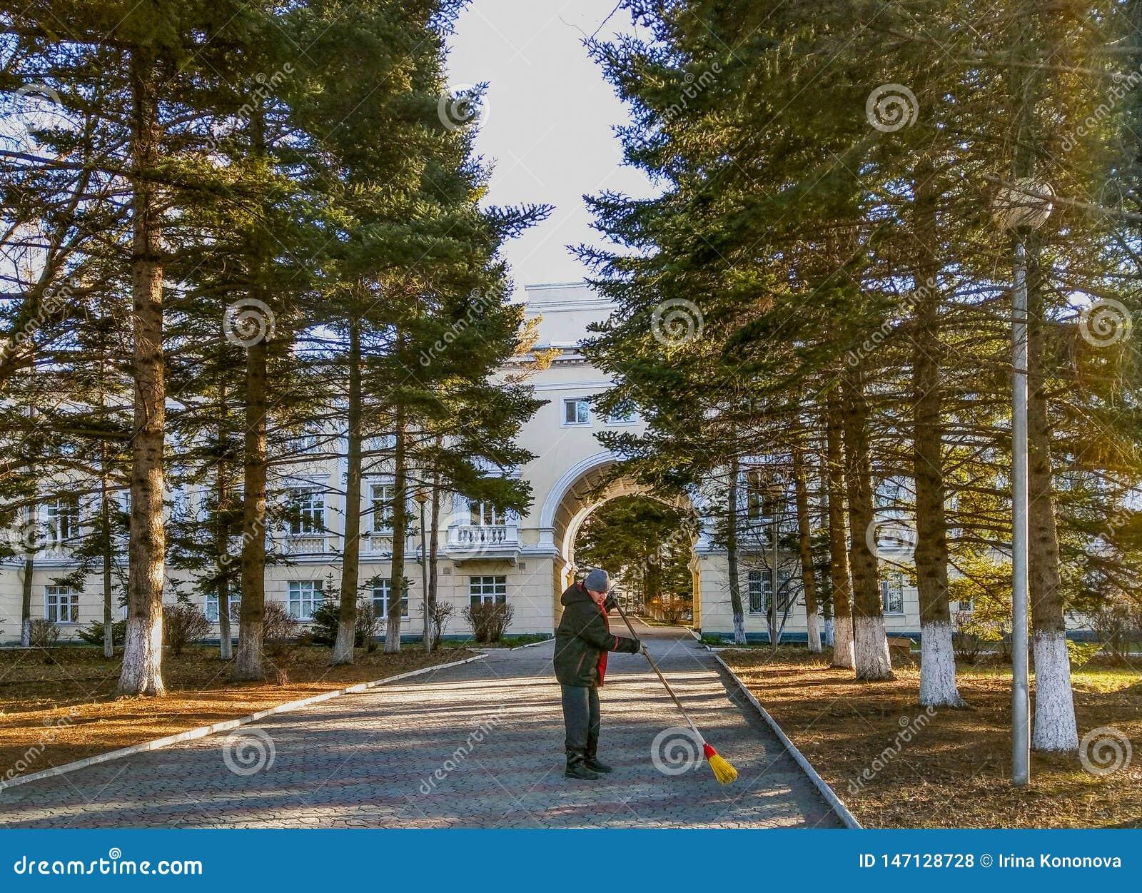 Un homme balaye un chemin au bâtiment de sanatorium avec un balai