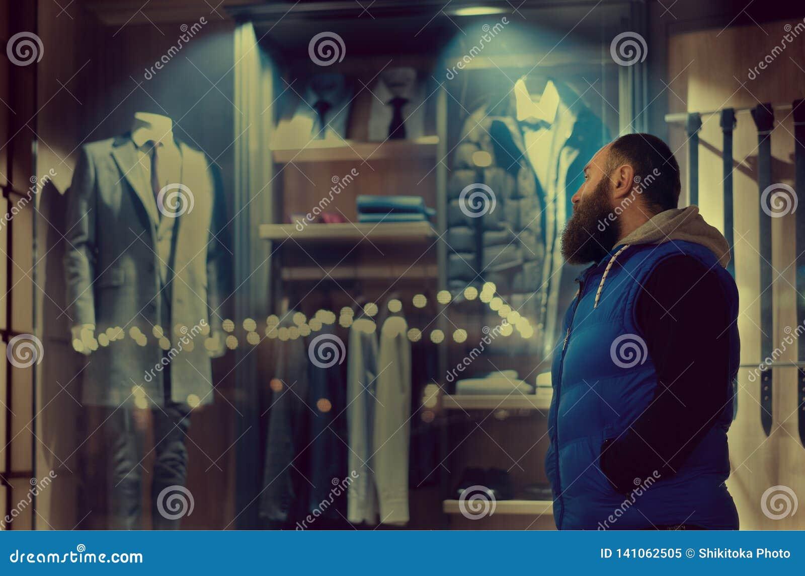 Un homme barbu dans des regards de sporstwear à la fenêtre de magasin avec l habillement d affaires