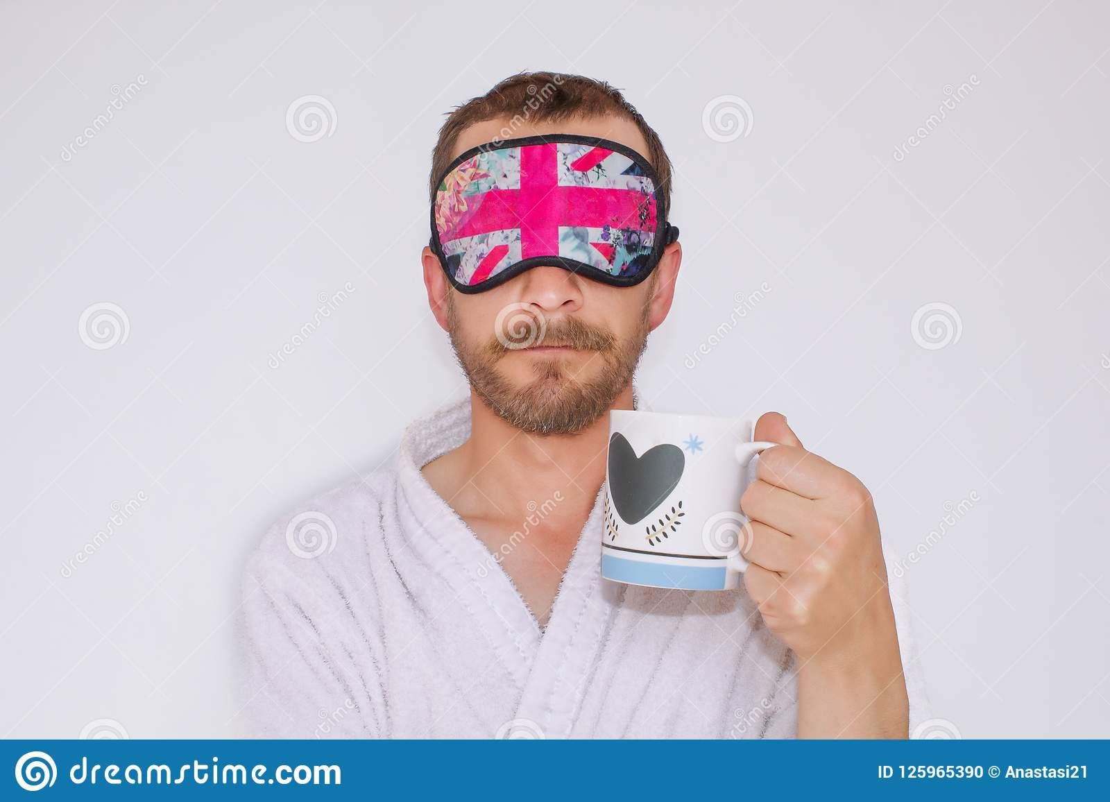 18a94bda09778 Un homme barbu dans une robe de chambre et un masque sur ses yeux, tenant