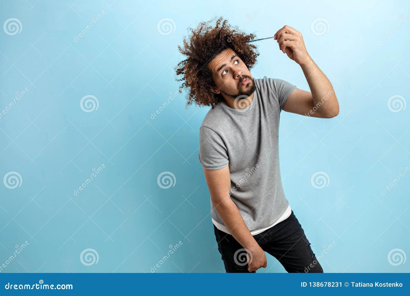 Un homme bel aux cheveux frisés utilisant un T-shirt gris se tient avec un regard et un contact réfléchis et concentrés ses