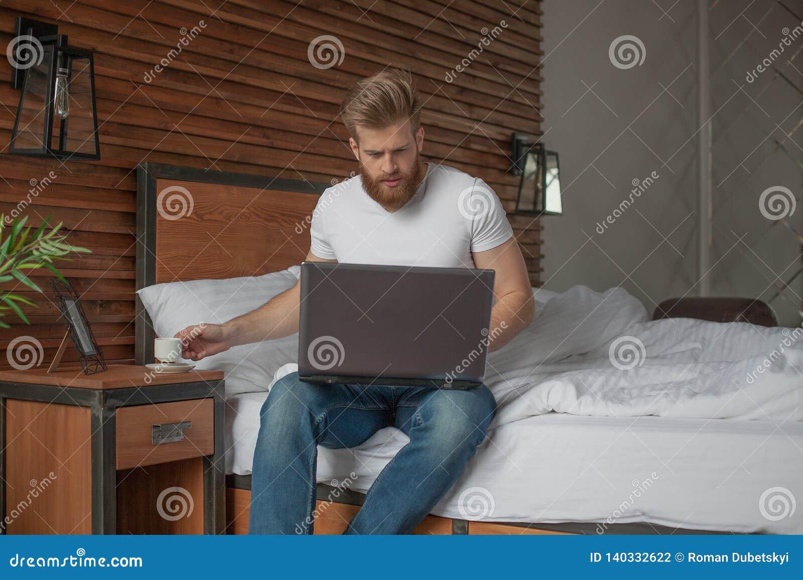 Un homme bel s assied au bord du lit avec un ordinateur dans des ses mains