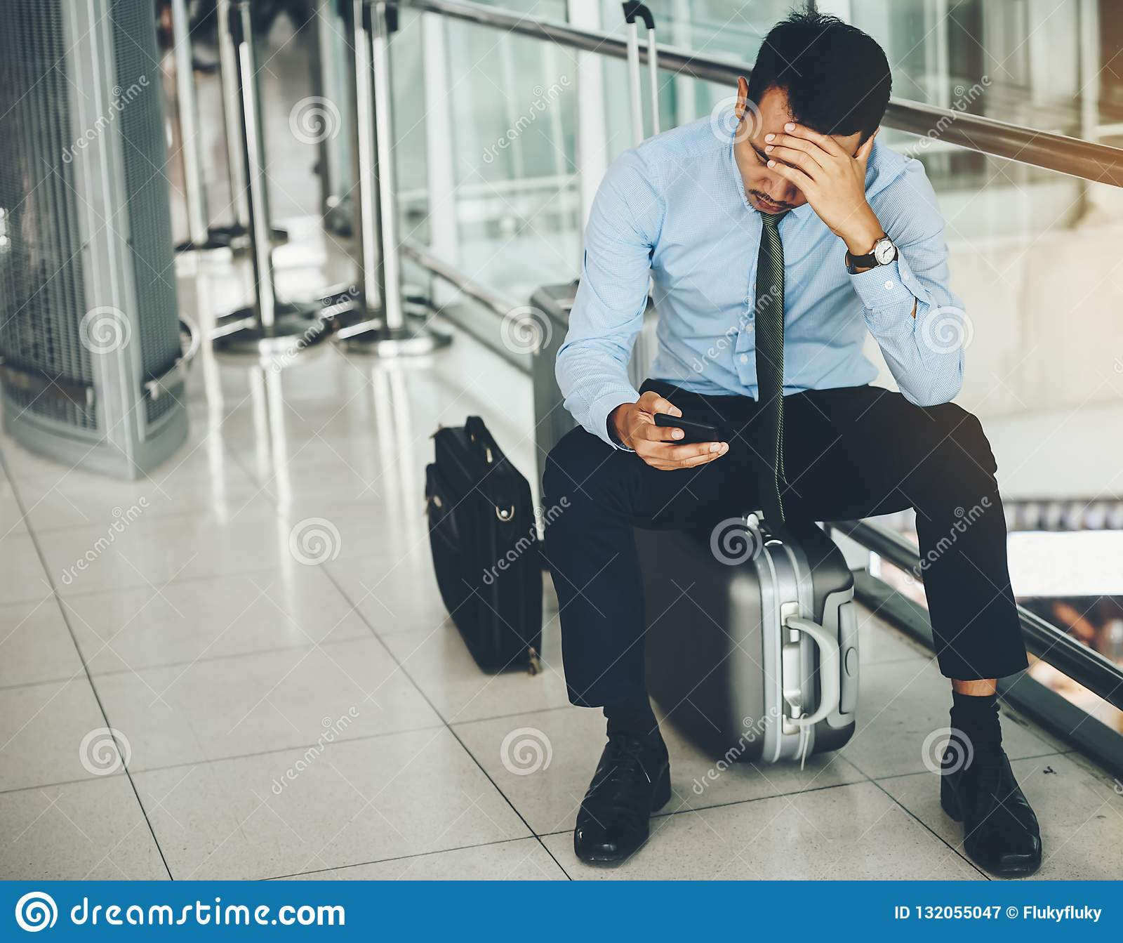 Un homme d affaires asiatique s assied sur son bagage Il a été soumis à une contrainte
