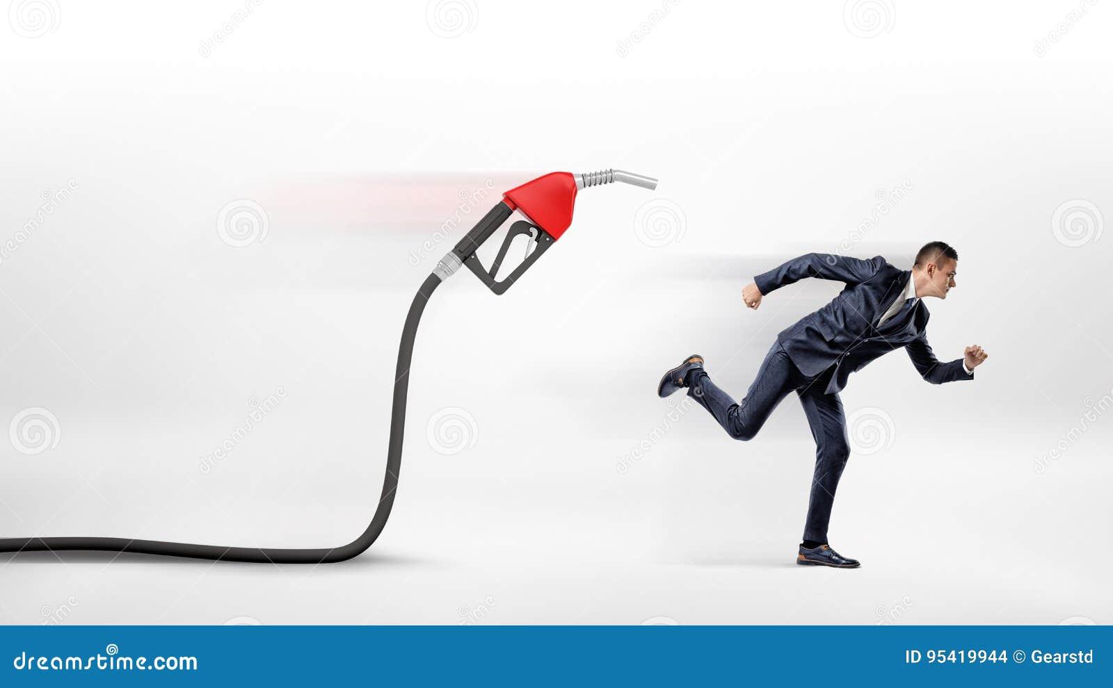 Un homme d affaires sur le fond blanc fonctionnant à partir d un bec de gaz rouge fixé à un tuyau noir
