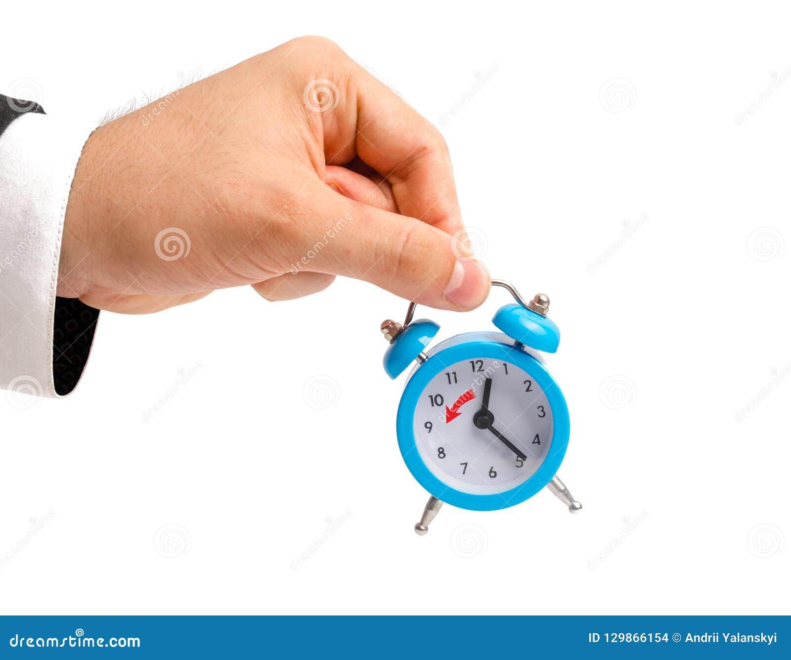 Un homme d affaires tient un réveil Transition à l horaire d hiver, transfert des heures à une heure de retour Montre à dispositi