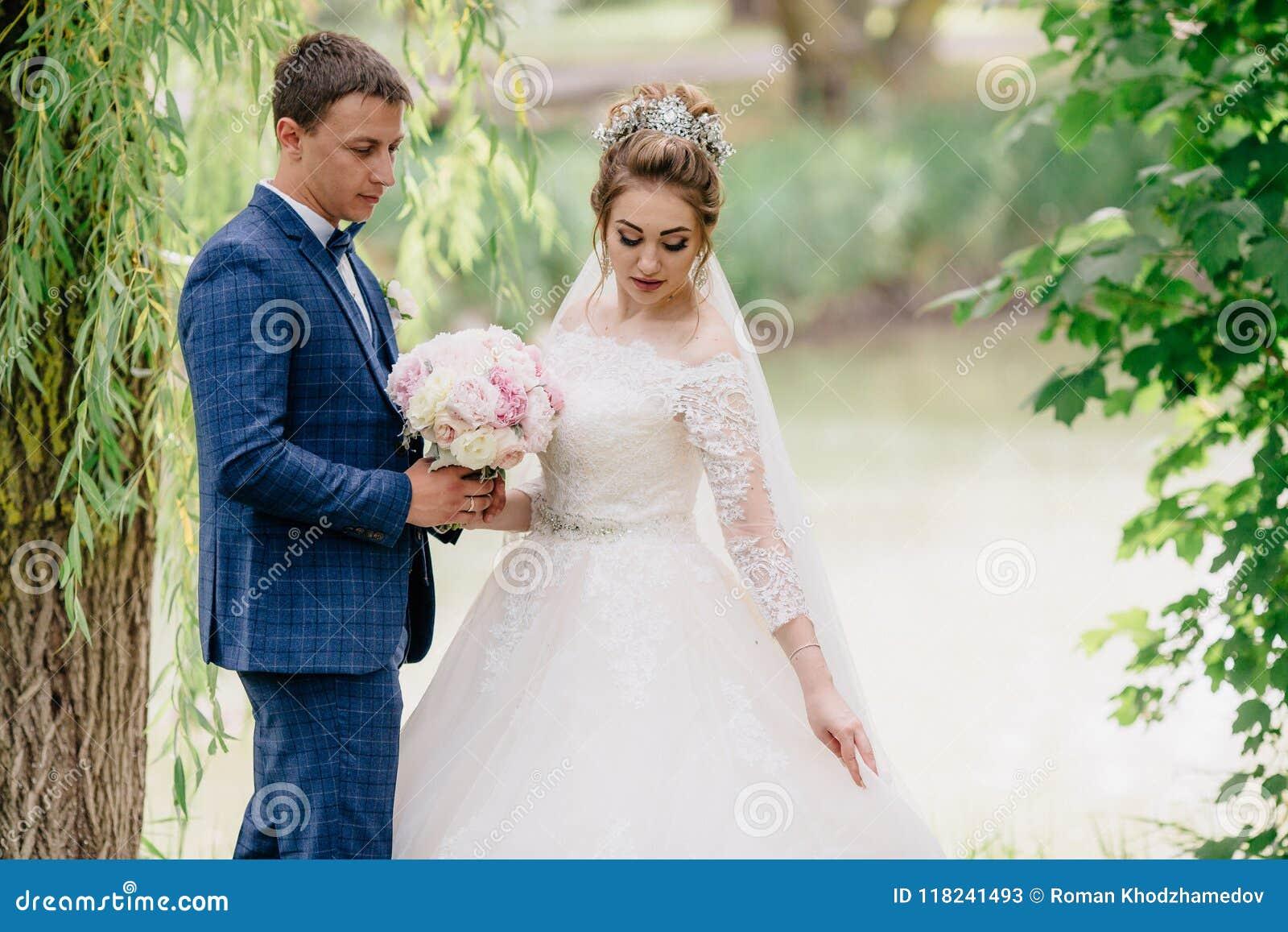 Un homme dans un costume de plaid admire sa robe de mariage du ` s d épouse et l aide à garder un bouquet des pivoines La jeune m