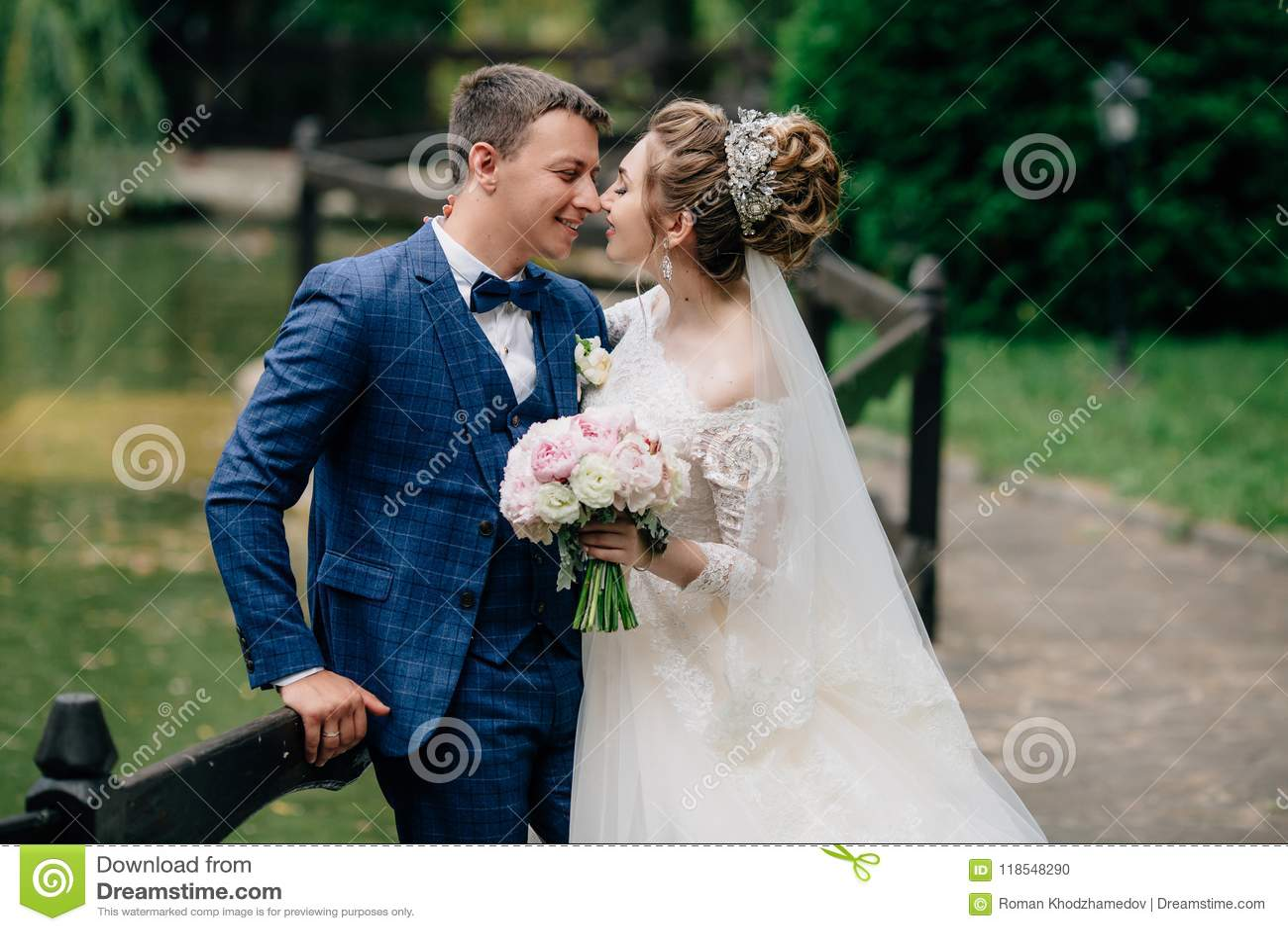 Un homme dans un costume moderne et une fille dans une robe de mariage embrassent et se dorent dans l un l autre leur jour du mar