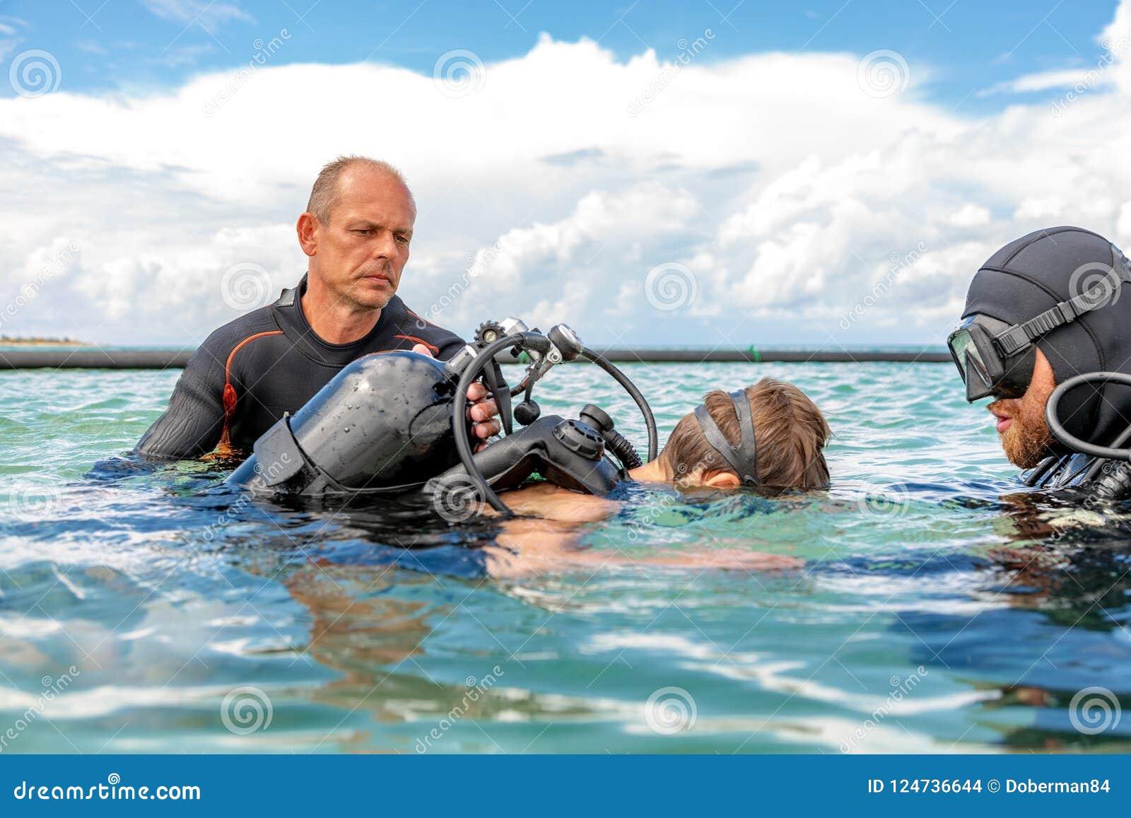 Un homme dans un costume pour plonger dispose un garçon à plonger