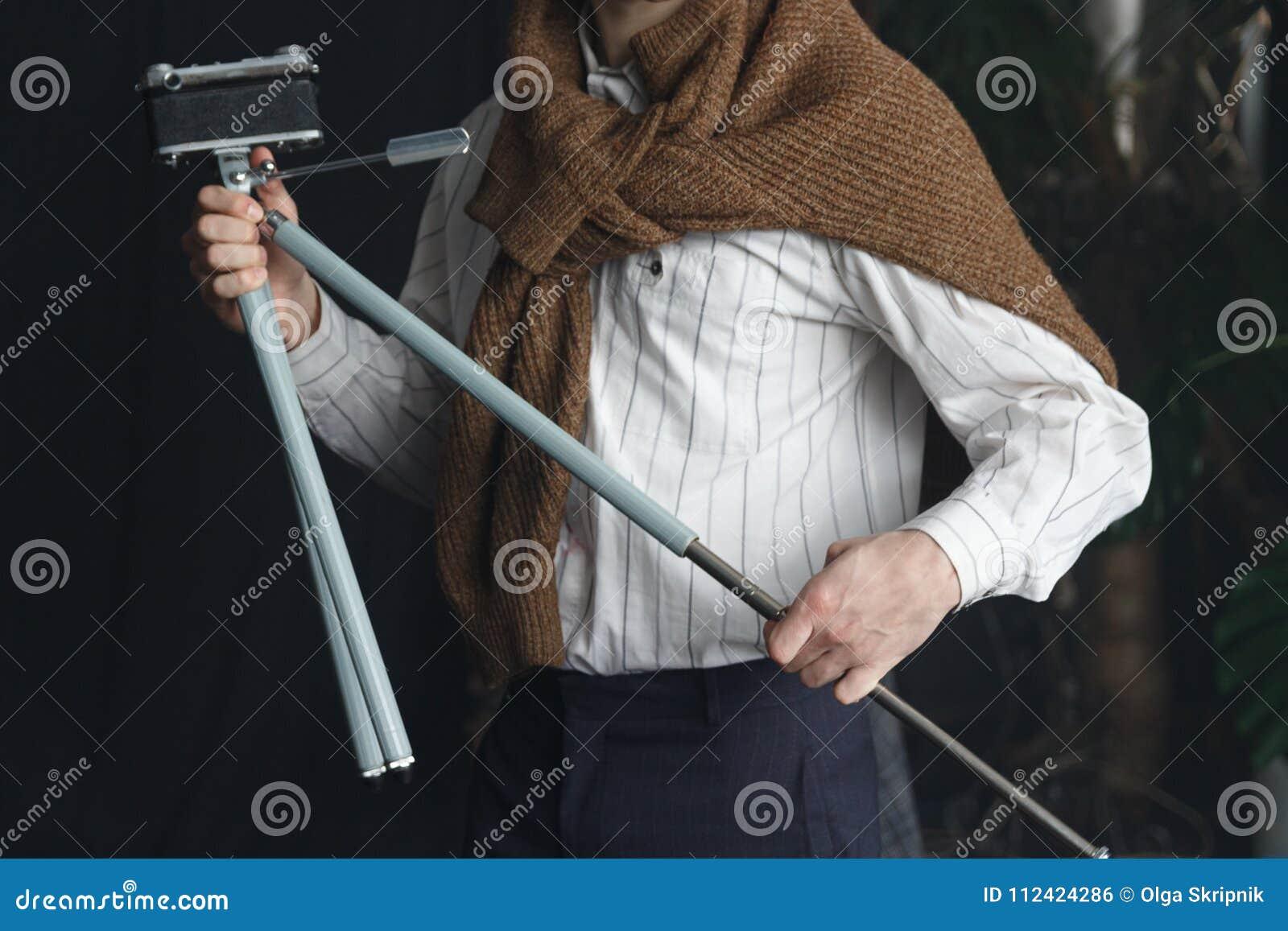 Un homme dans une chemise blanche et un chandail brun tient un vieux trépied avec un appareil-photo, un vintage