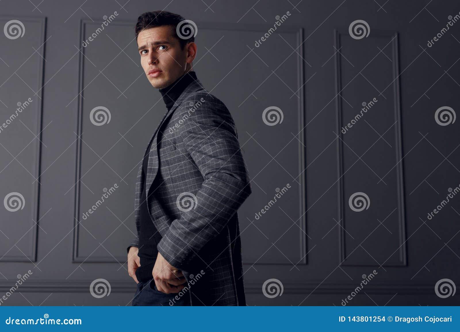 Un homme dans une veste et un col roulé châle-gris, se tenant dans le profil avec des mains dans des ses poches et semblant sûrs