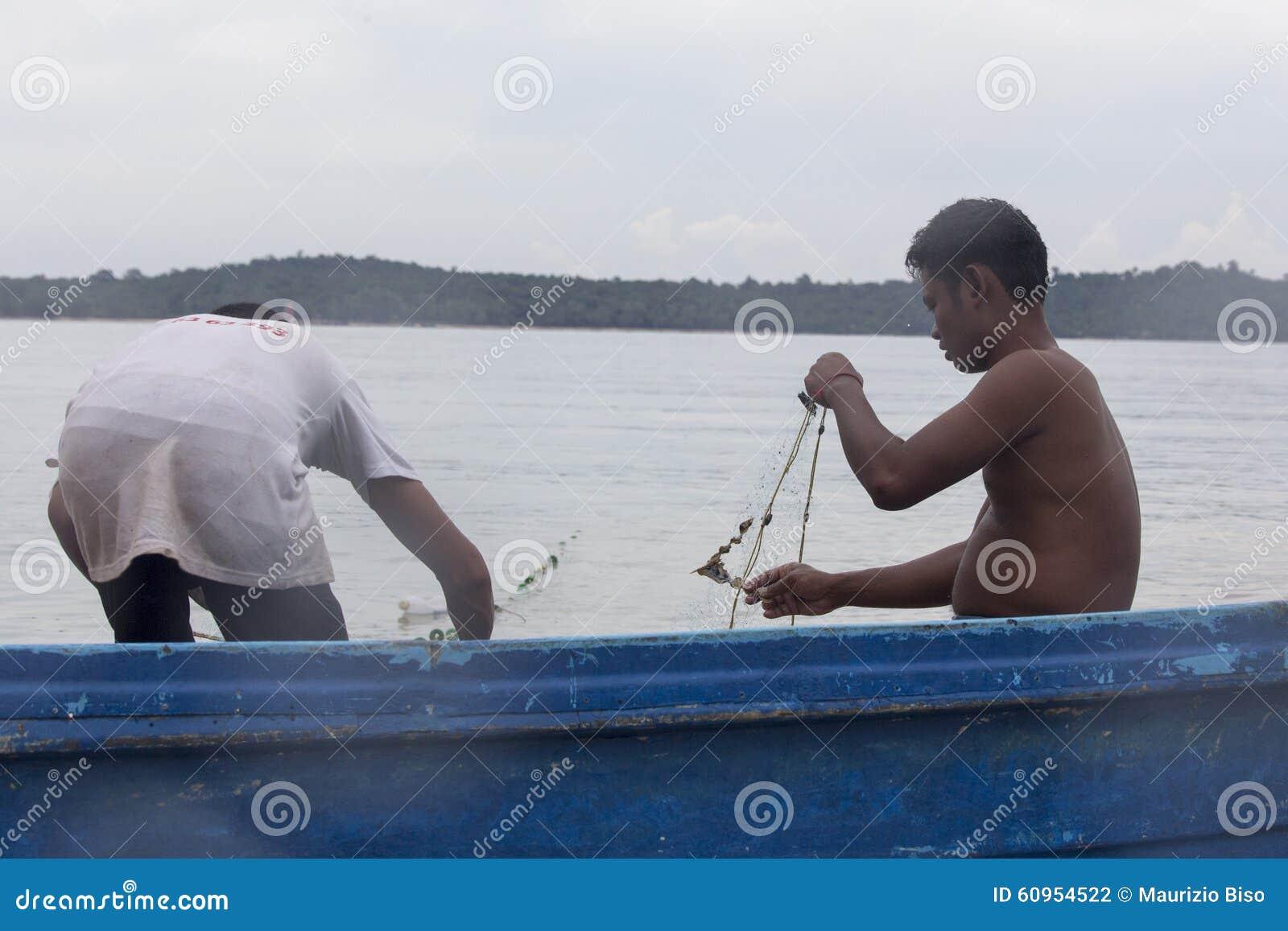 Un homme de pêcheur se tient sur son bateau avec une pile de filet de pêche