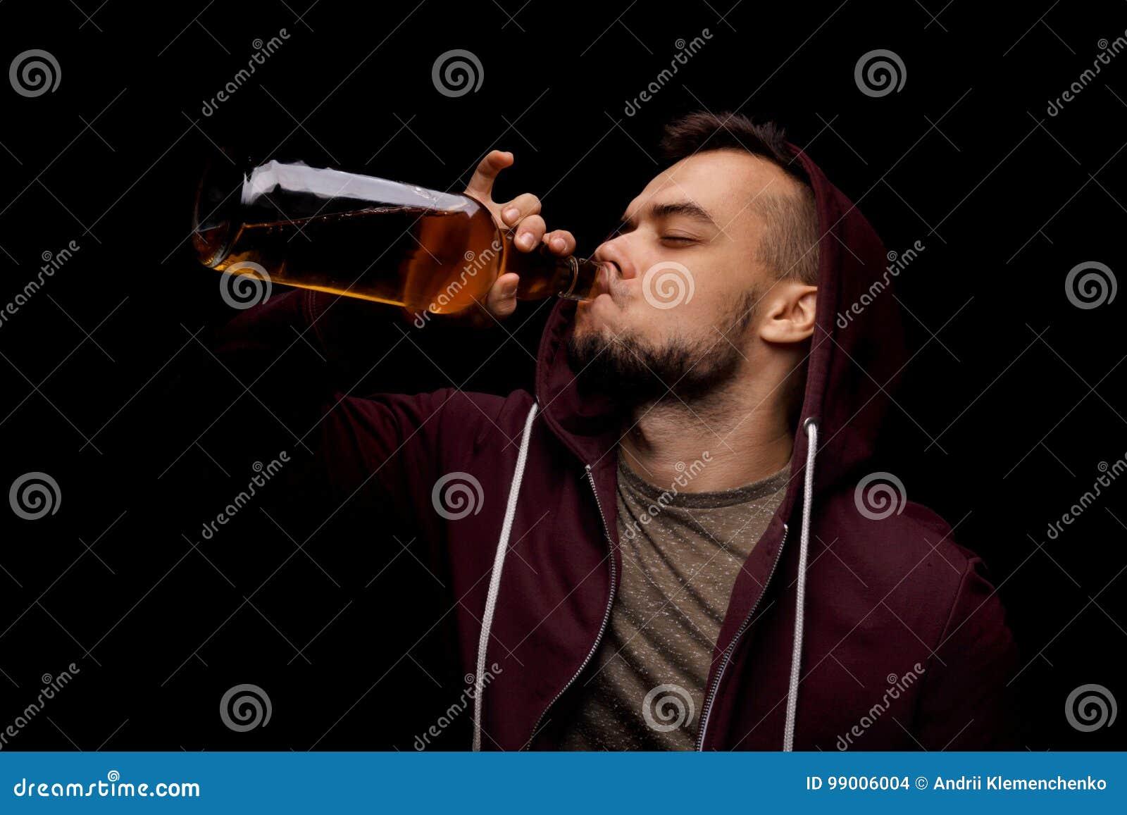 Un homme de risque boit du whiskey sur un fond noir Une personne à charge déprimée de type sur l alcool Copiez l espace
