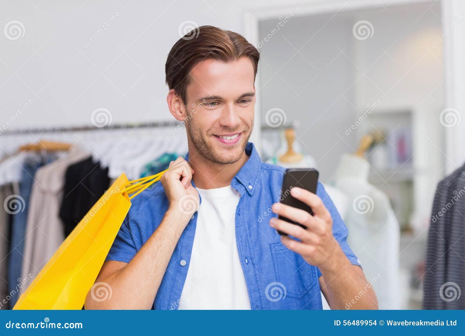 Un homme de sourire avec des paniers regardant son smartphone