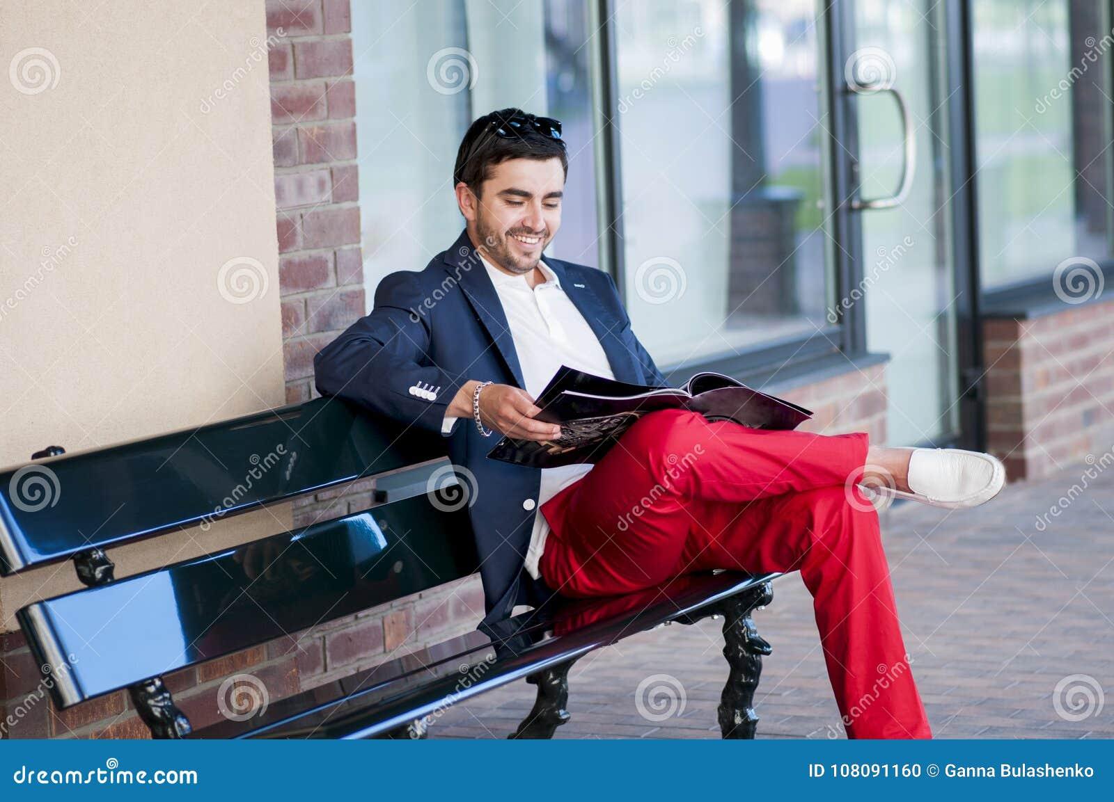 un homme de sourire charismatique lit un magazine sur un banc photo stock image du mode m le. Black Bedroom Furniture Sets. Home Design Ideas