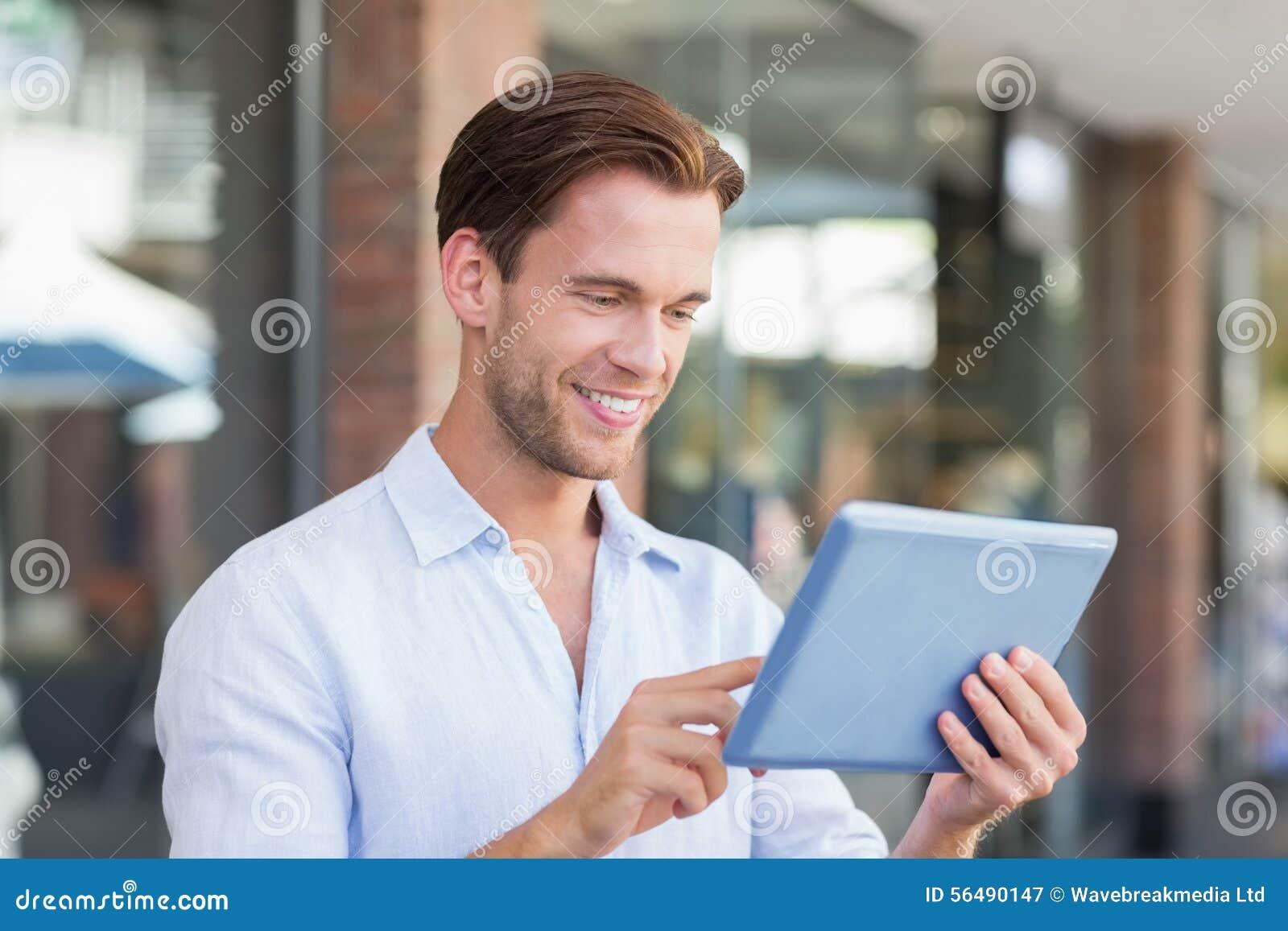 Un homme de sourire heureux à l aide de son comprimé