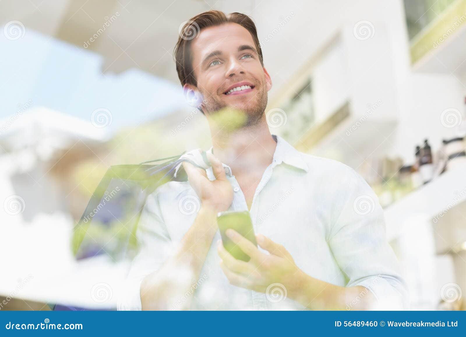 Un homme de sourire heureux regardant le téléphone