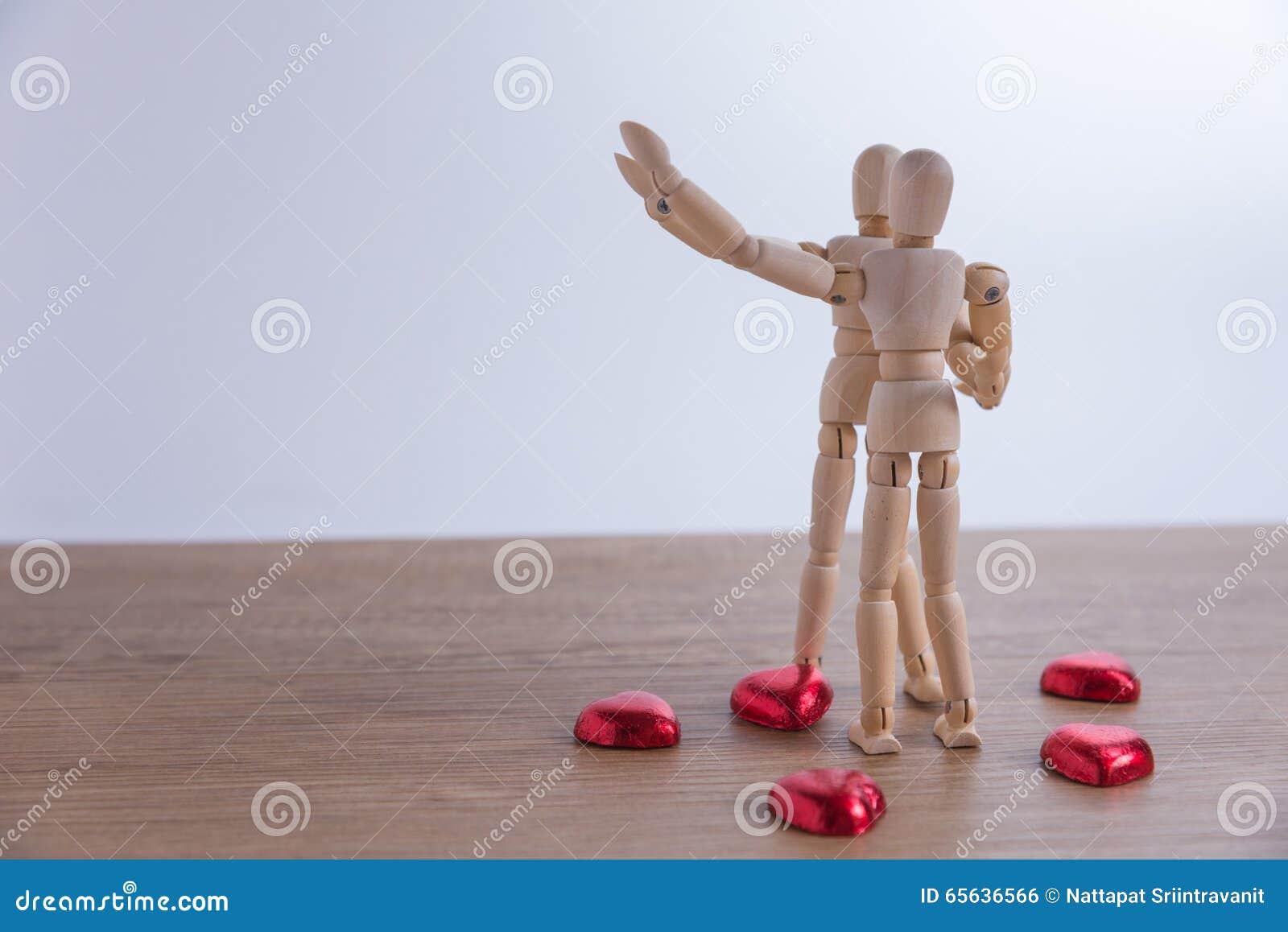 Un homme en bois de poupée avec du chocolat en forme de coeur dans le Saint Valentin