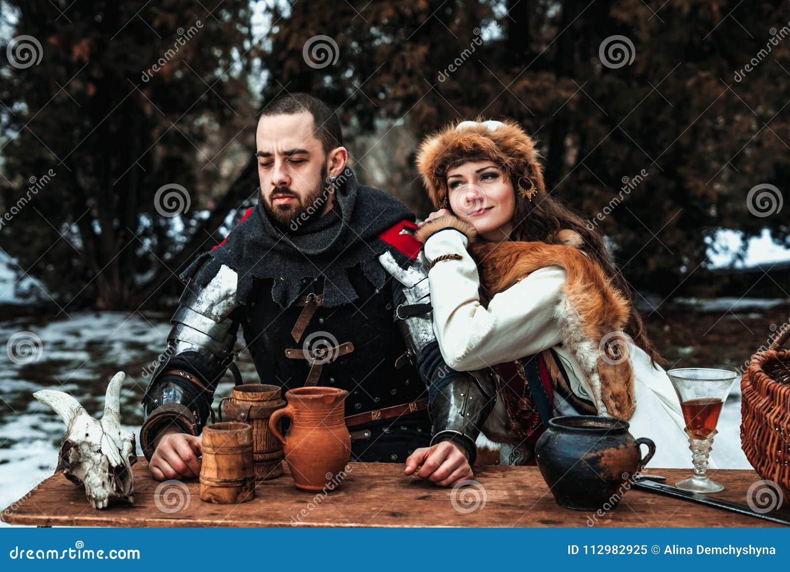 Un homme et une femme dans des costumes historiques s asseyent à une table