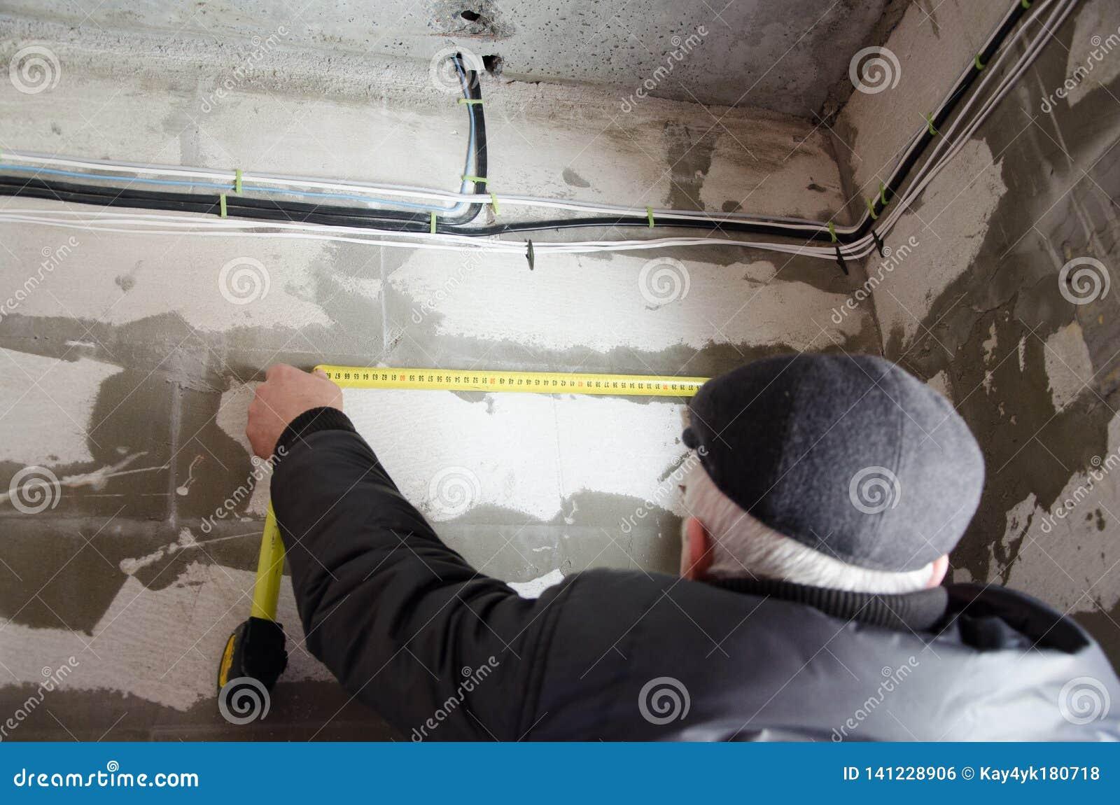 Un homme mesure le câblage, exactitude est important