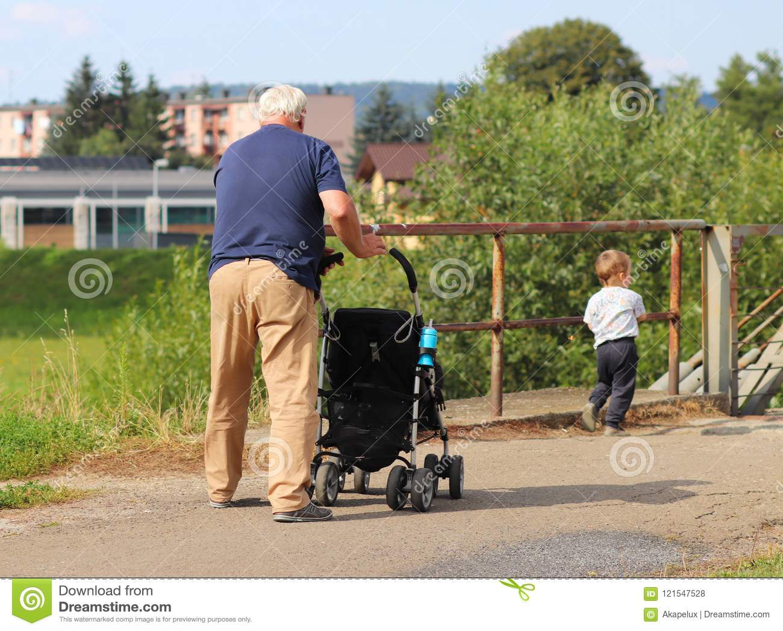 Un homme plus âgé marche avec son petit-fils sur la nature poussant une poussette de bébé devant lui La famille se repose en natu