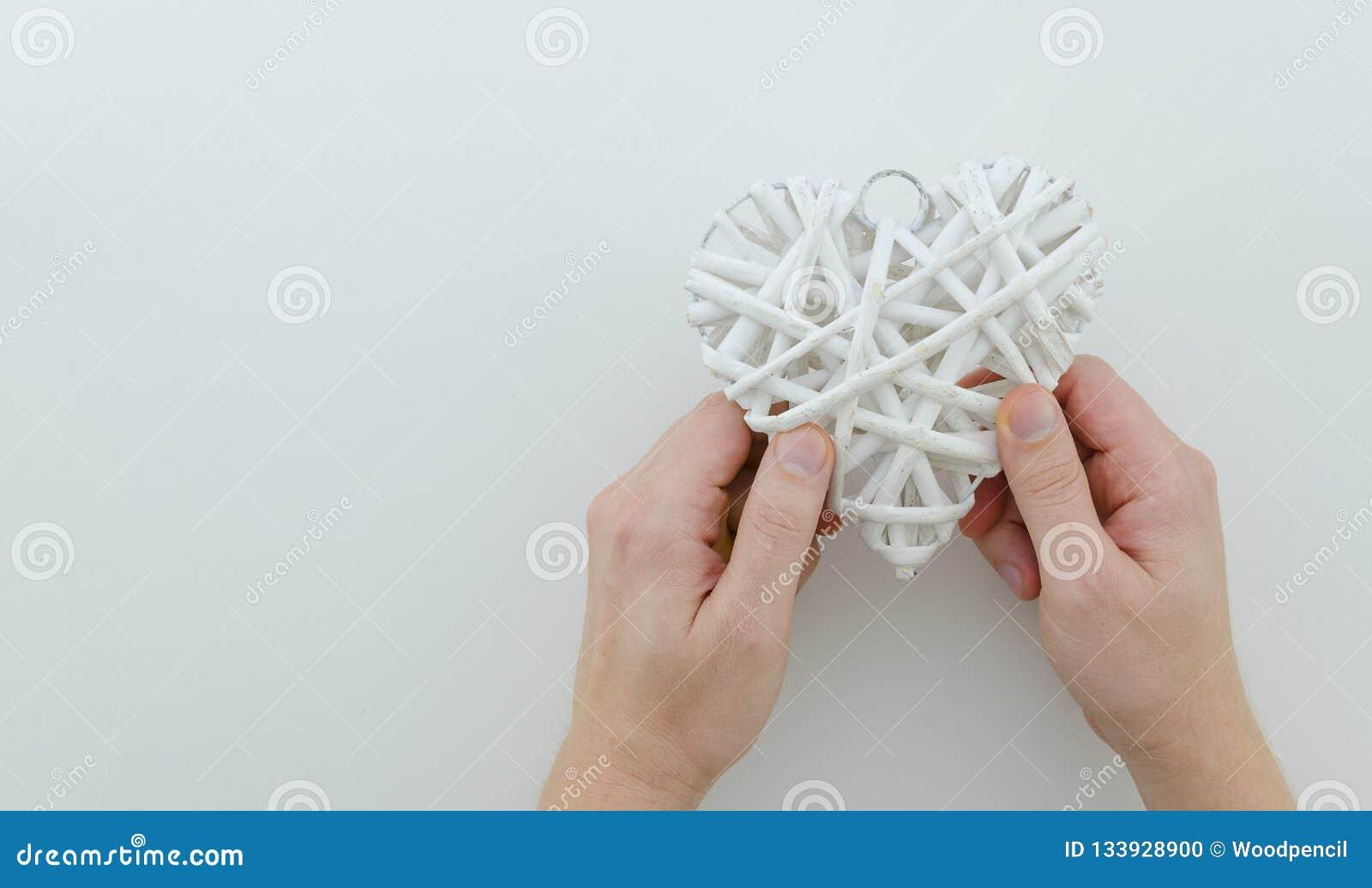 Un homme tient un coeur blanc en osier avec les deux mains Maquette pour des vacances, Noël, merci donnant le jour, valentine, an