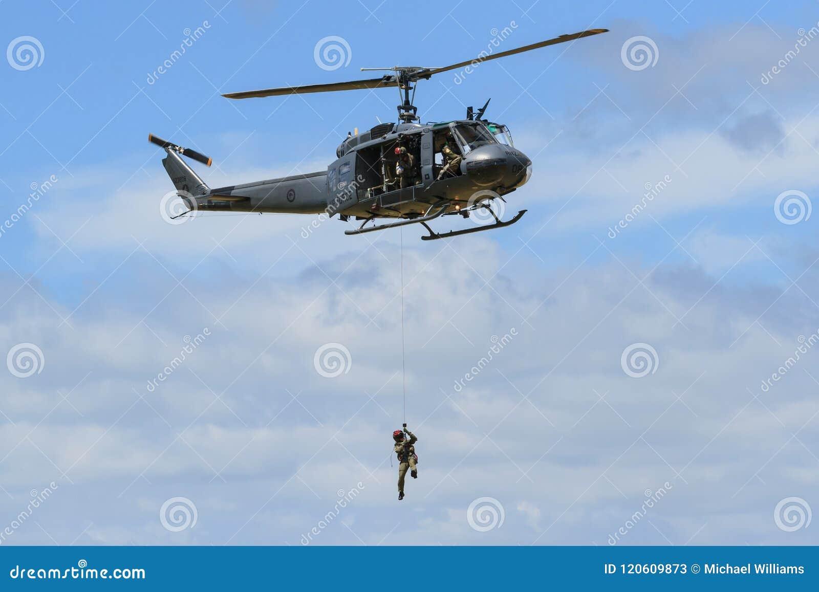 Un homme winched vers le bas d un hélicoptère d Iroquois de Bell