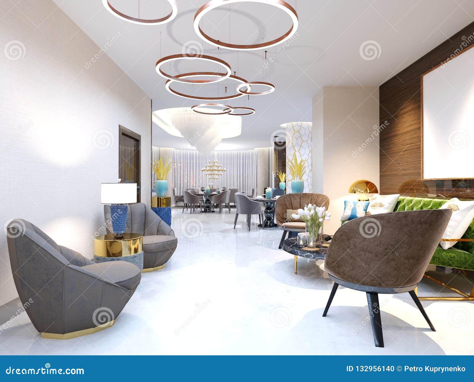 Un hotel moderno con un área y un salón de recepción con las sillas tapizadas grandes del diseñador y una lámpara grande de anill