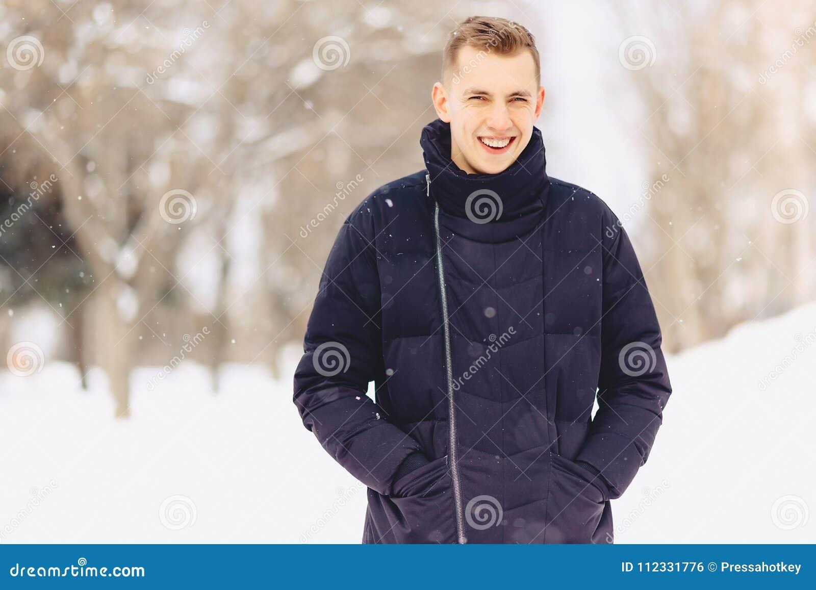 Un individuo con el pelo corto ligero en actitudes de una chaqueta del invierno a vino