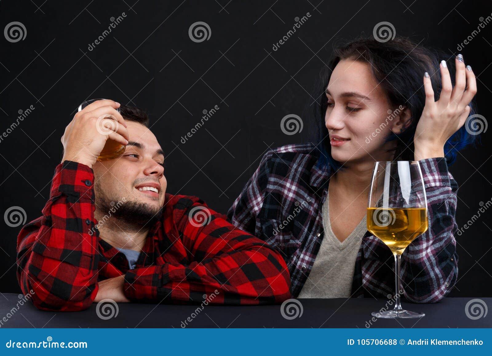 Un individuo con una muchacha relajada con alcohol en un contador de la barra en un fondo negro