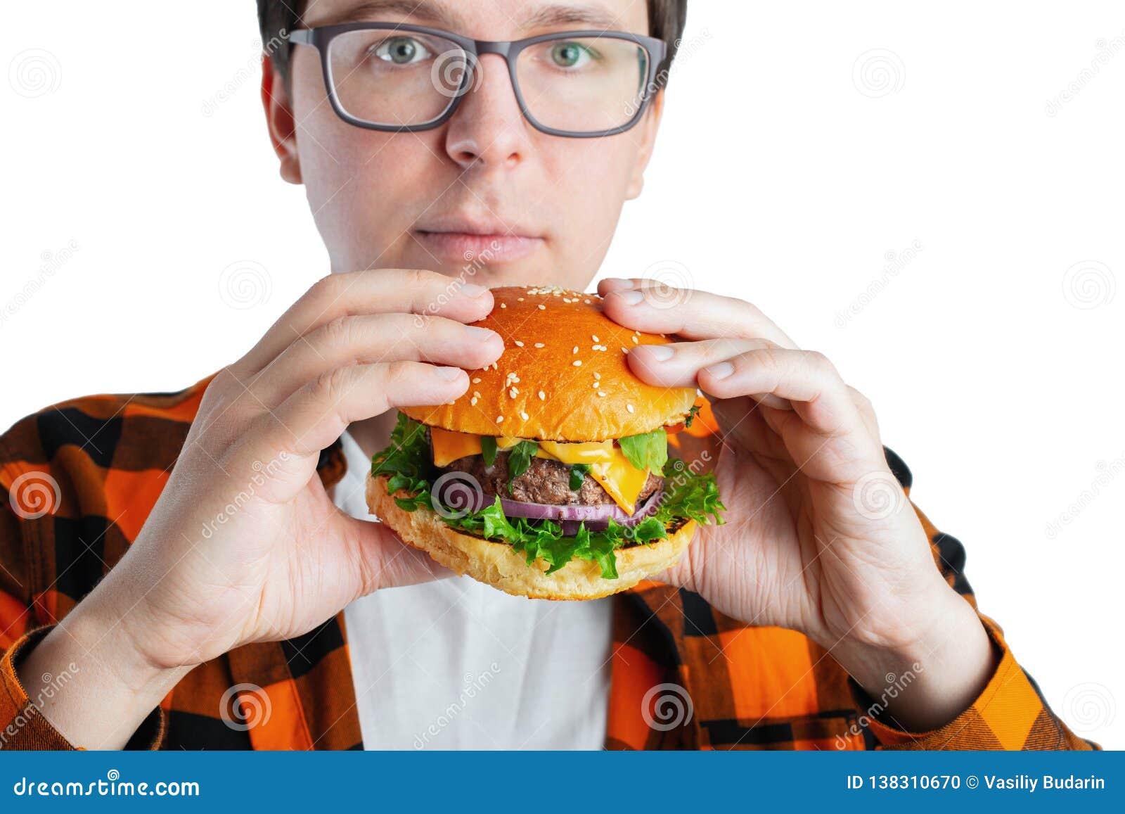 Un individuo joven con los vidrios que sostienen una hamburguesa fresca Un estudiante muy hambriento come los alimentos de prepar