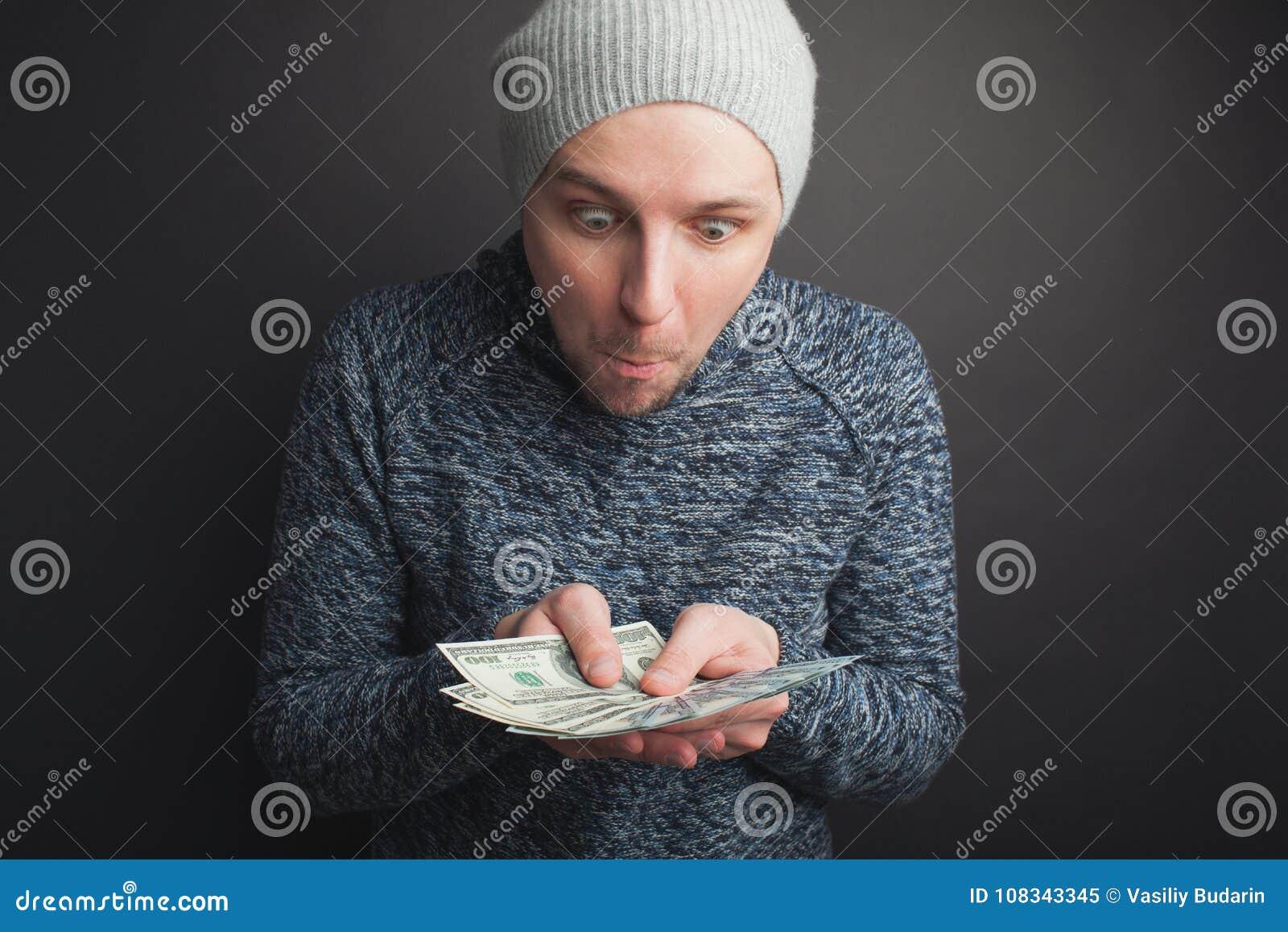 Un individuo joven en un casquillo gris y una barba, sosteniendo una pila de dinero y de miradas fijas en ella en un fondo negro