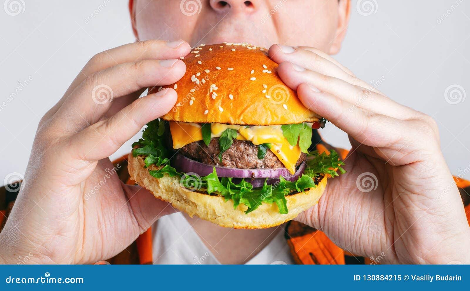 Un individuo joven está sosteniendo una hamburguesa fresca Un estudiante muy hambriento come los alimentos de preparación rápida