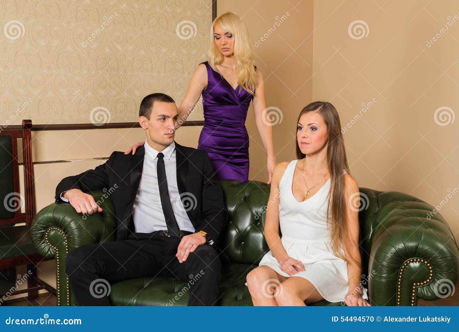 Un individuo y dos muchachas en el cuarto