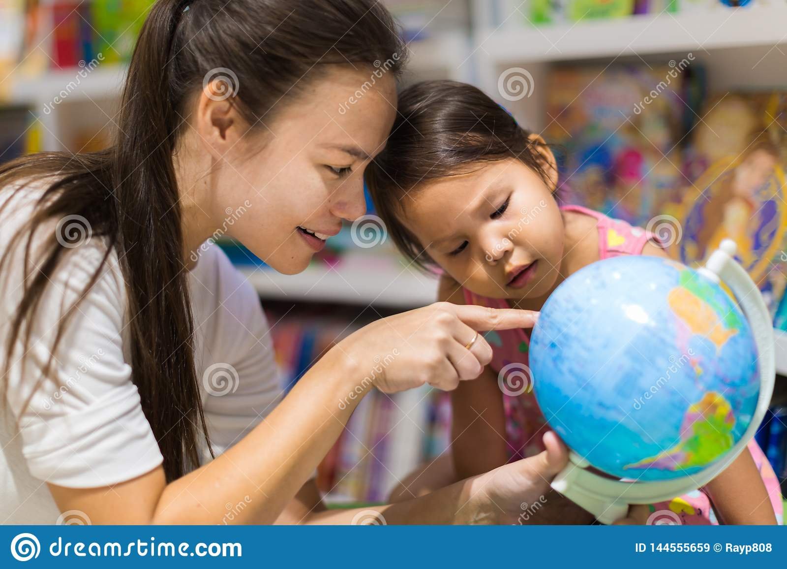 Un insegnante e uno studente prescolare che imparano geografia su un globo del mondo