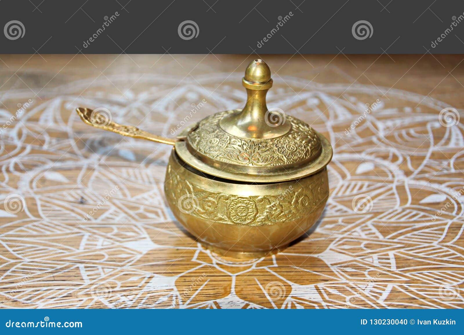 Un insieme per tè bevente, una tazza ed il tordo, coperti di coperchi bronzei, vista del primo piano