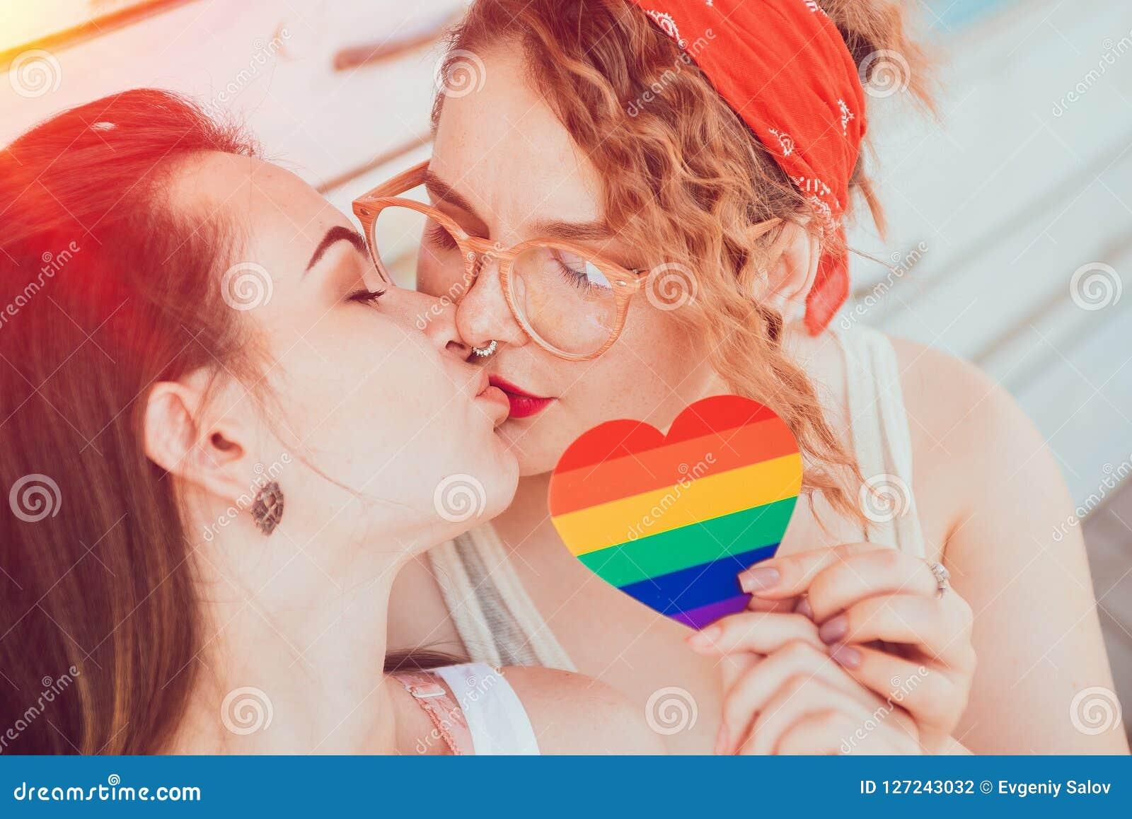 Un jeune couple lesbien embrassant et tenant un coeur avec le drapeau