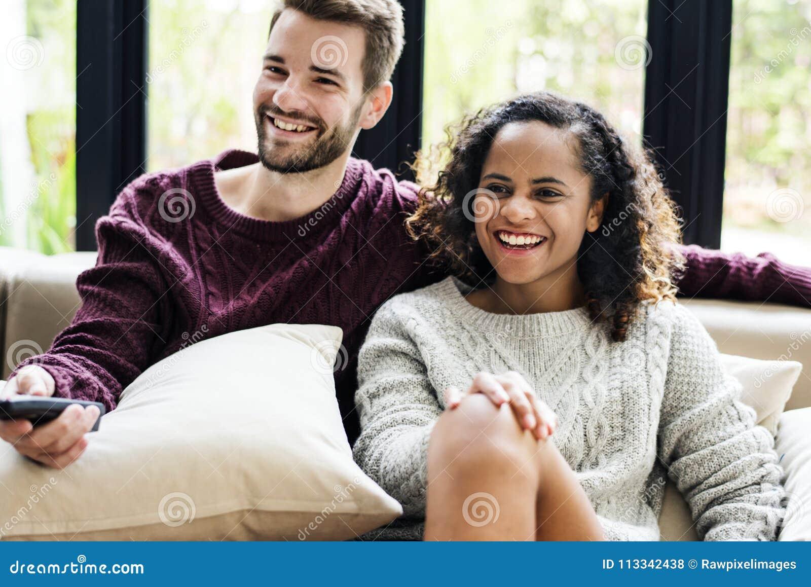 Un jeune couple observant une exposition de TV ensemble
