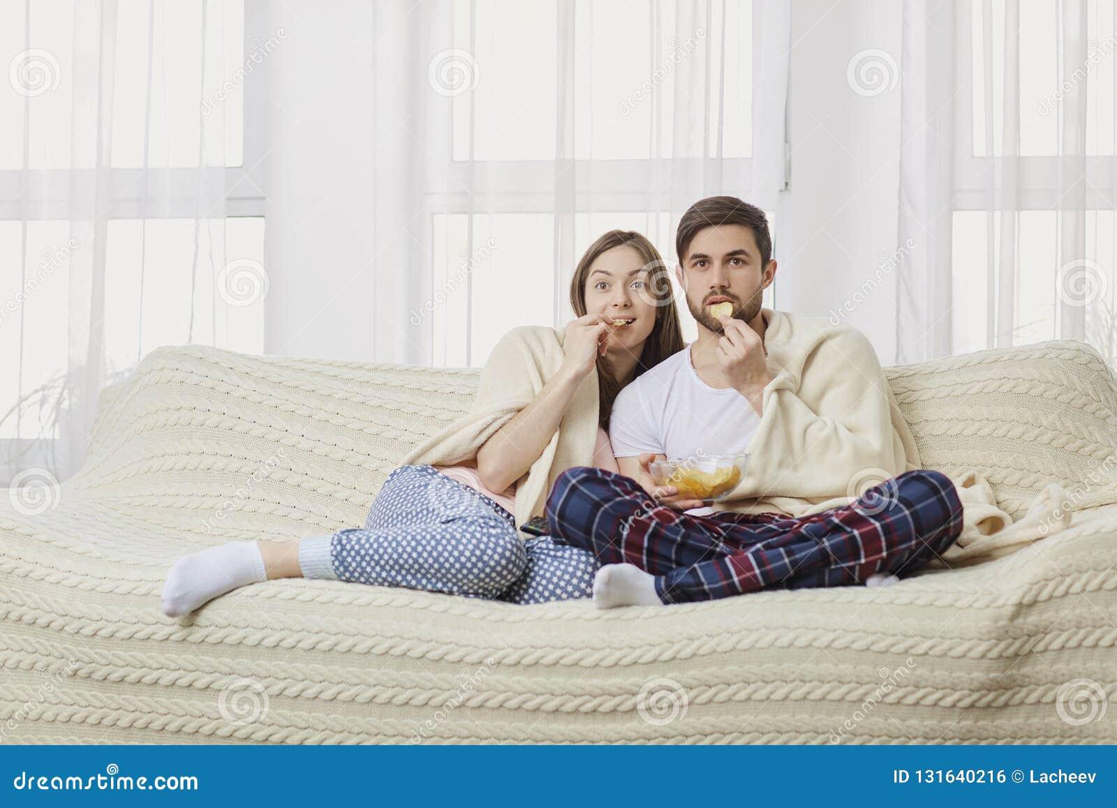 Un jeune couple se reposant sur le divan regardant une TV intéressante