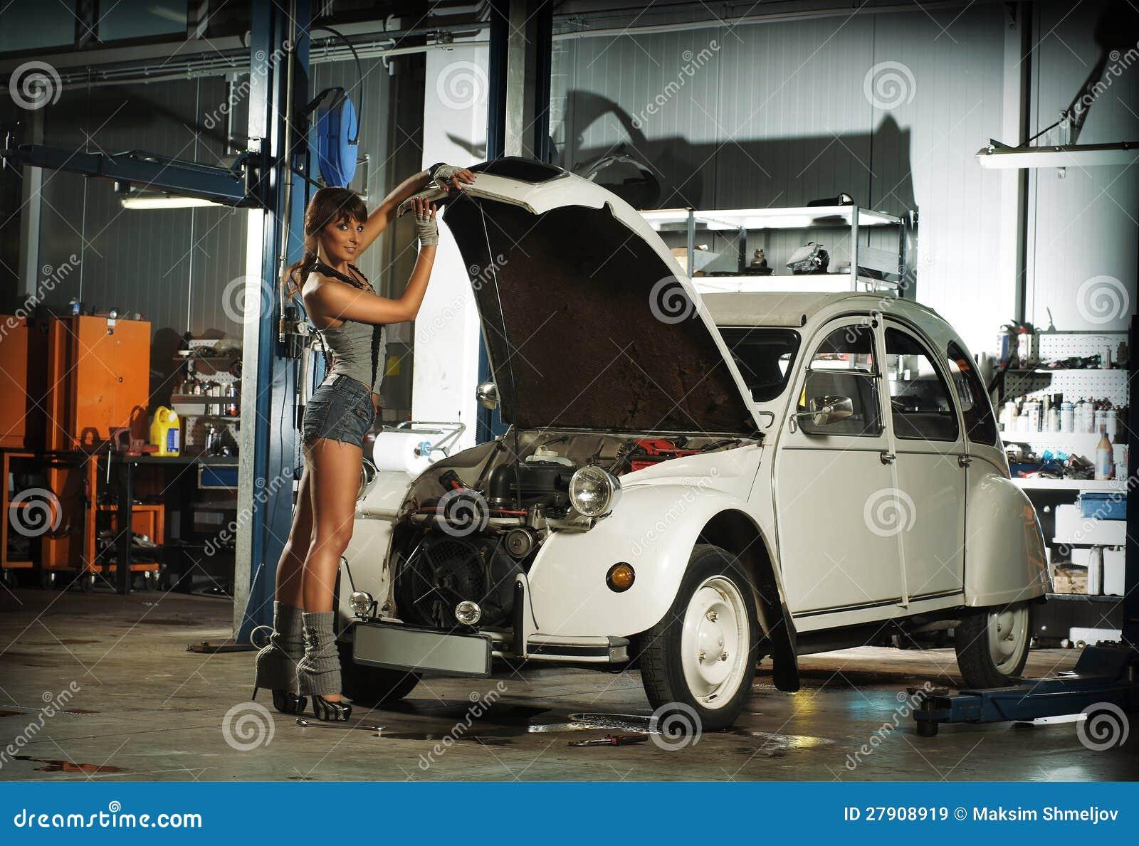 Un jeune femme r parant un r tro v hicule dans un garage for Voiture dans un garage