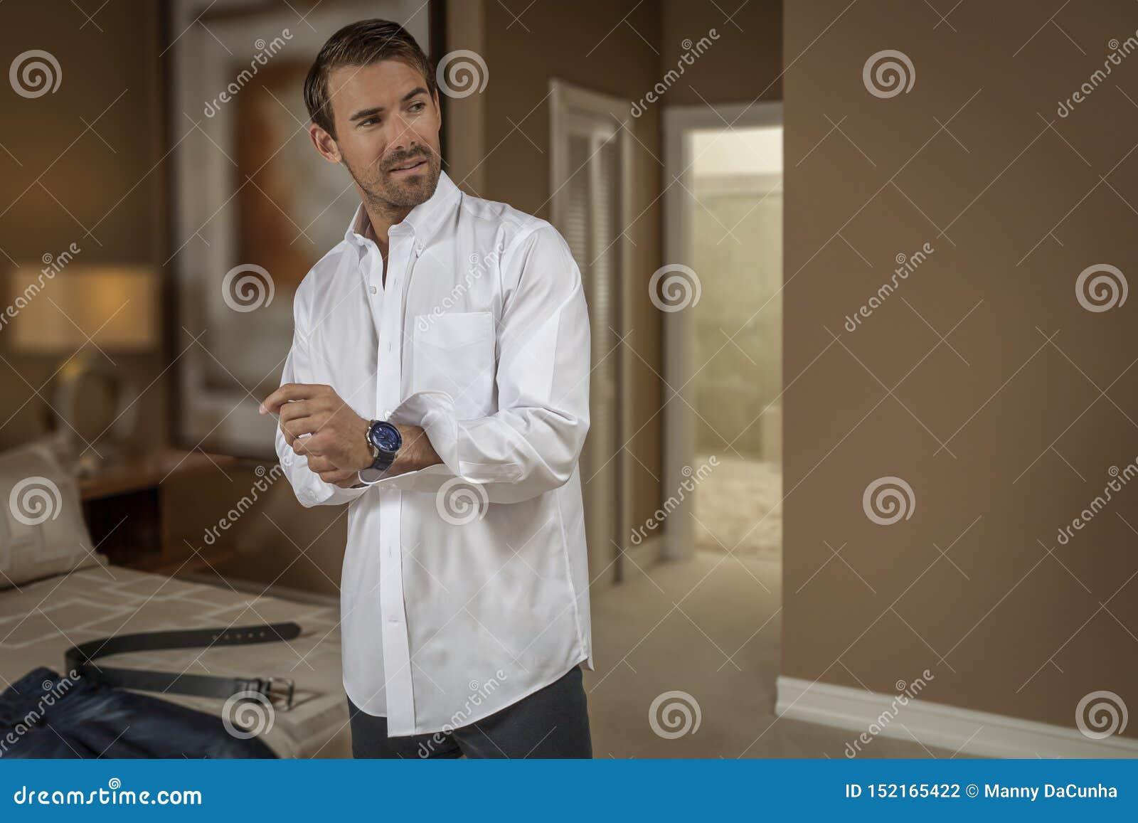 Un jeune homme beau obtient habillé dans la chambre à coucher